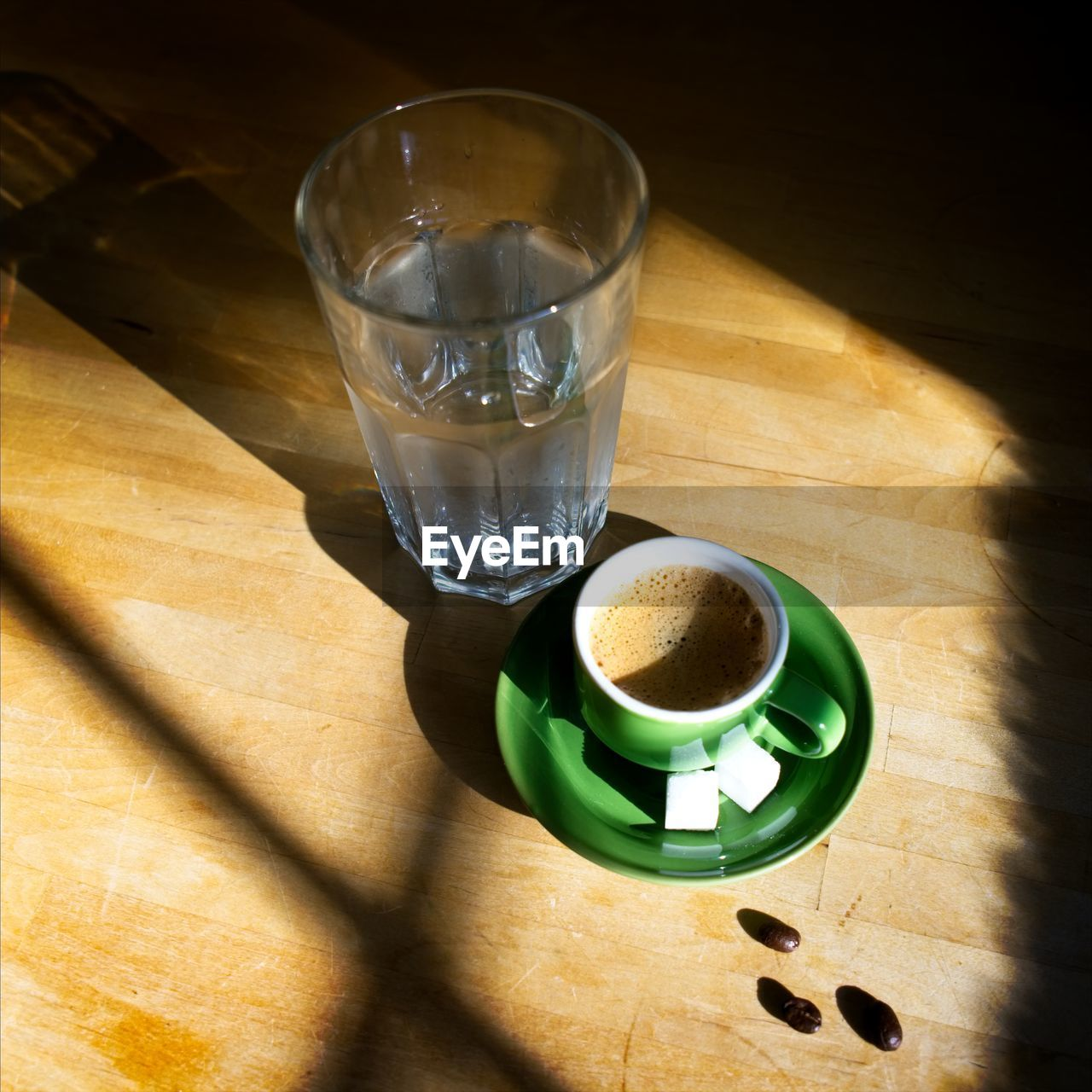 High Angle View Of Coffee Cup With Drinking Glass On Wooden Table During Sunny Day