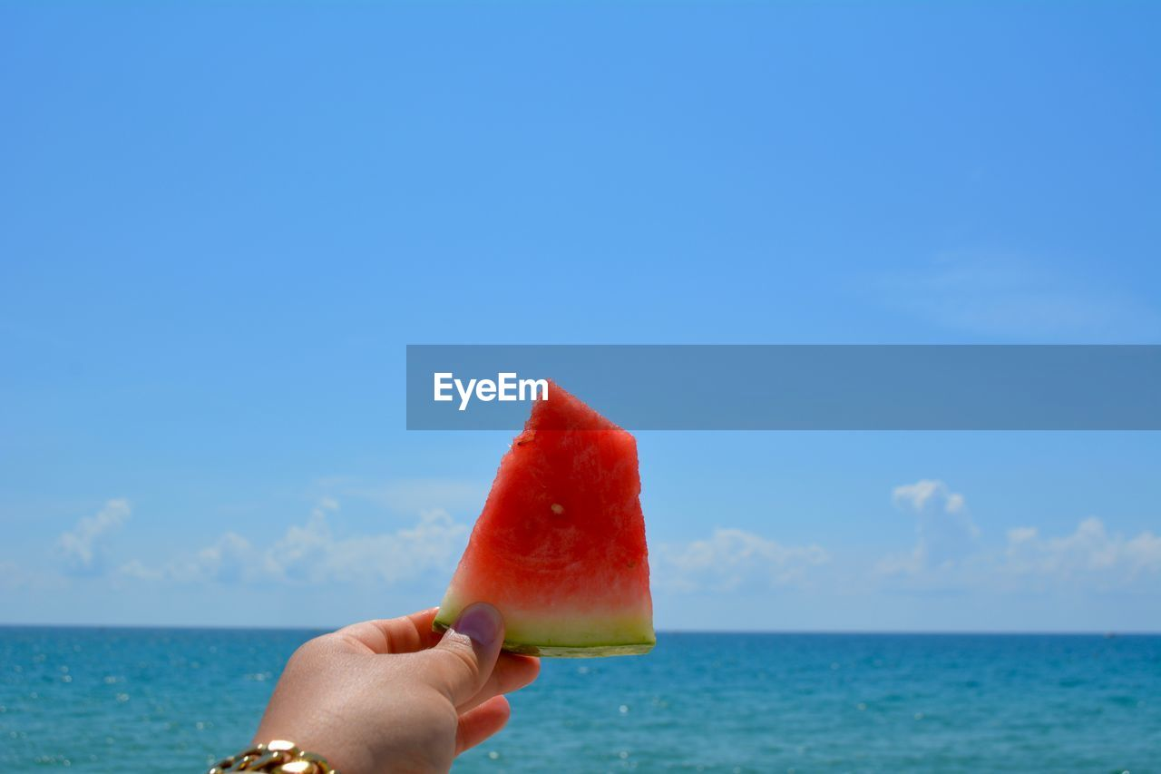 human body part, human hand, one person, hand, holding, sky, food, food and drink, real people, fruit, unrecognizable person, red, sea, lifestyles, day, water, body part, nature, leisure activity, watermelon, horizon over water, finger, outdoors