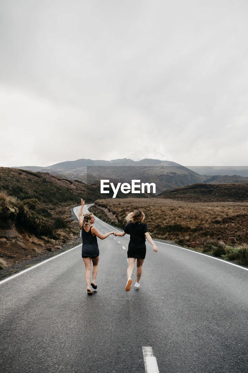 Friends walking on road against sky