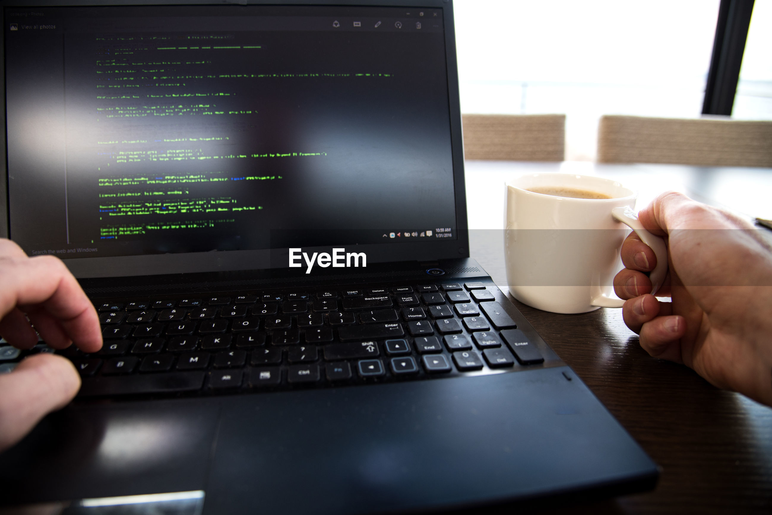 Cropped image of hands using laptop and holding coffee cup on table