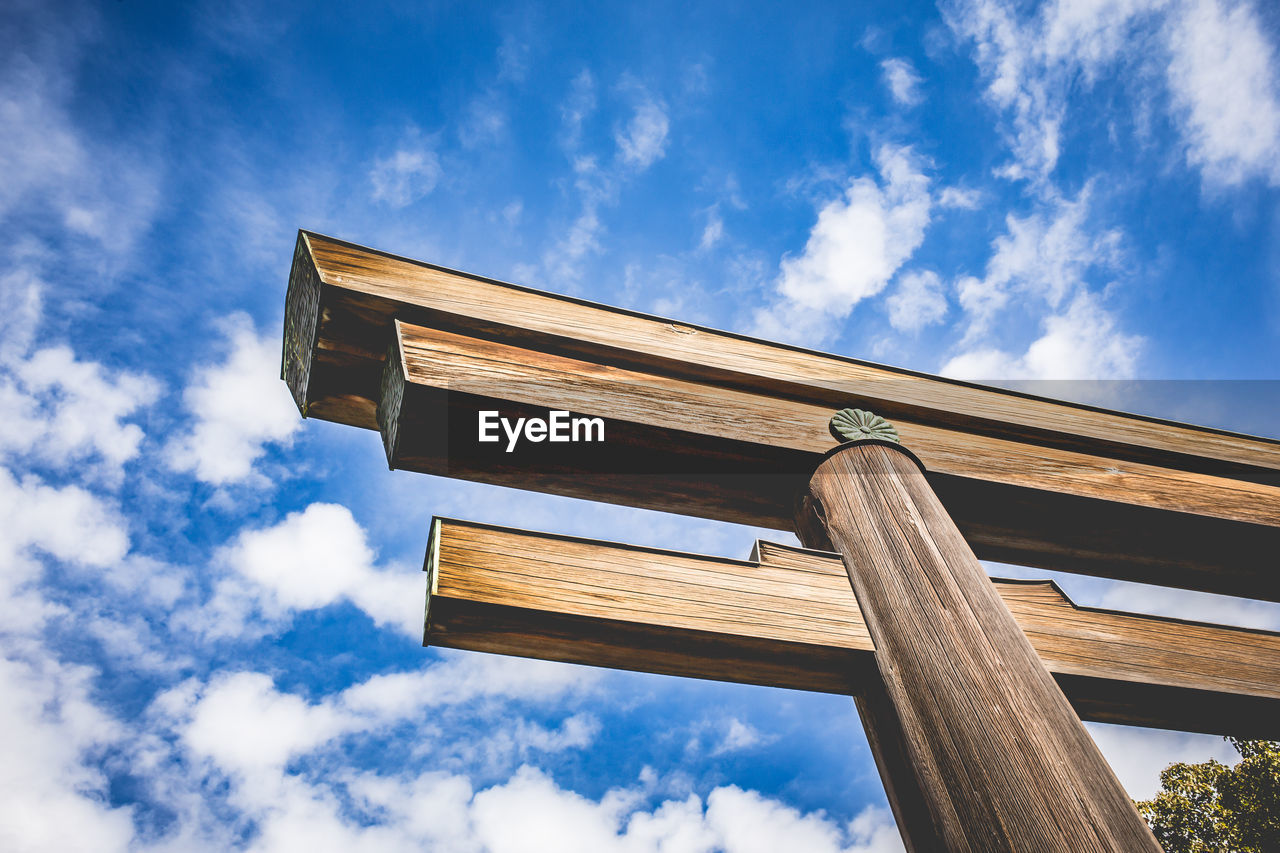 Low Angle View Of Wooden Torii Against Cloudy Blue Sky
