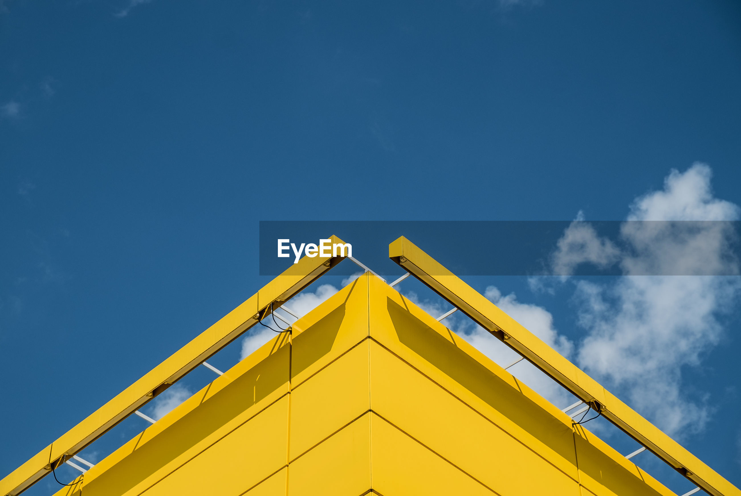 Low angle view of yellow built structure against blue sky