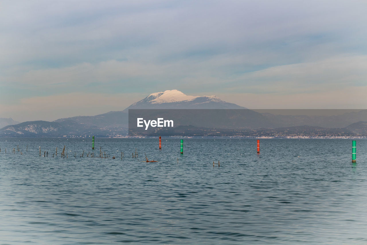 water, sky, mountain, cloud - sky, scenics - nature, waterfront, sea, beauty in nature, nature, tranquility, nautical vessel, tranquil scene, day, non-urban scene, transportation, mountain range, buoy, outdoors, mode of transportation, floating on water