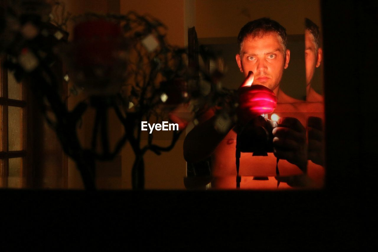Man holding illuminated candle while standing in front of mirror
