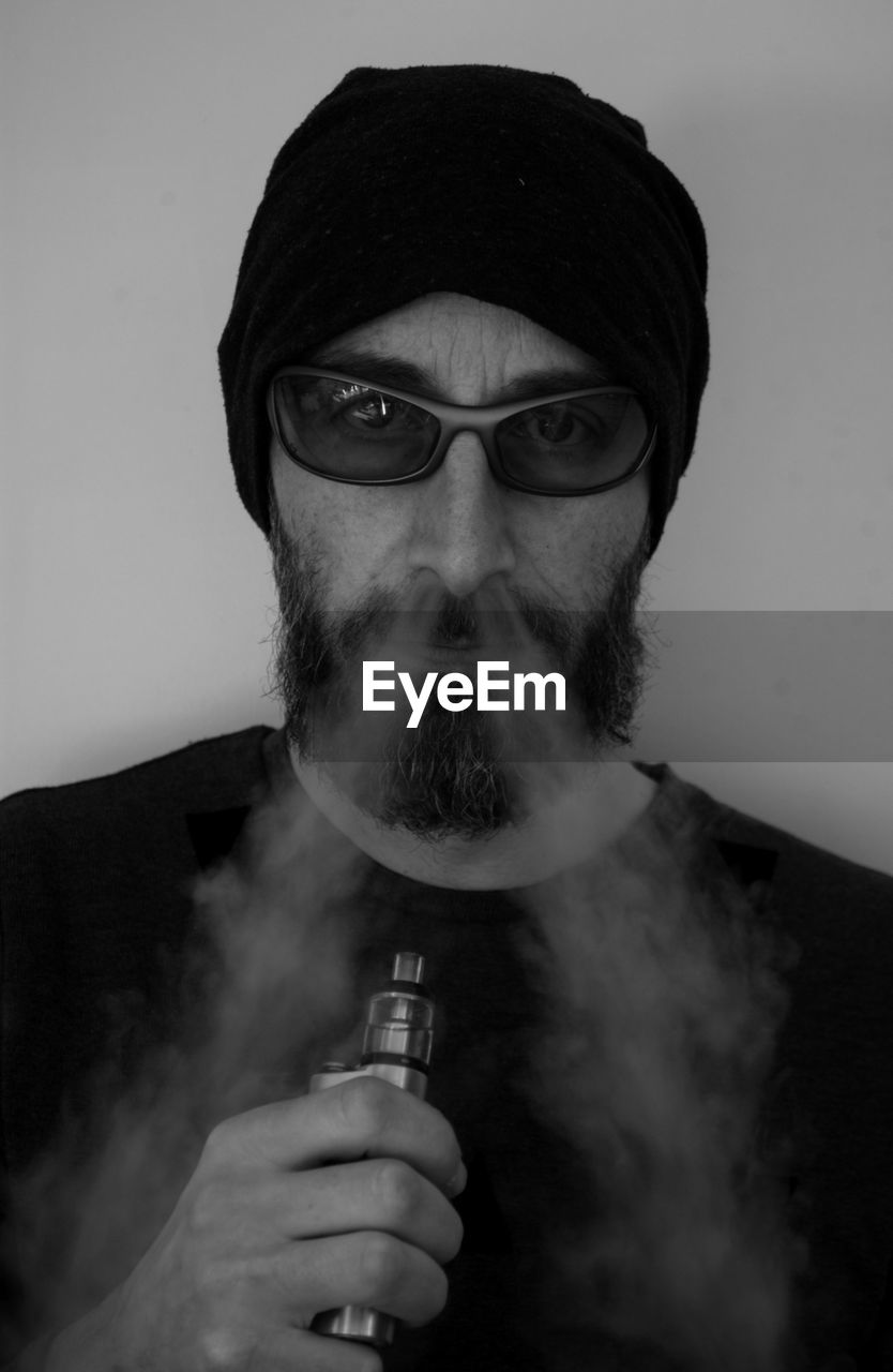 Portrait of man smoking electronic cigarette against gray background