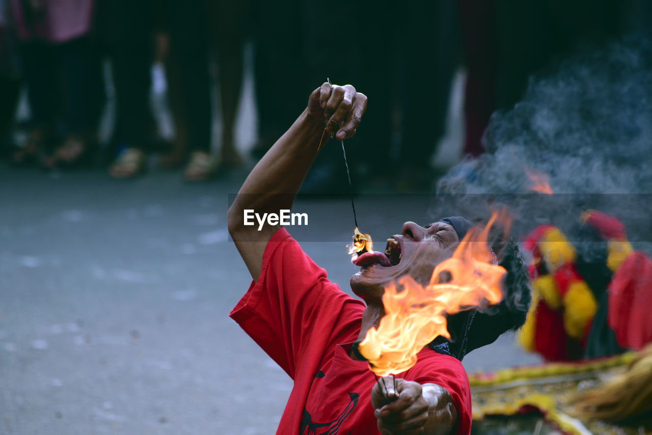 Male Fire Dancer Performing On Road