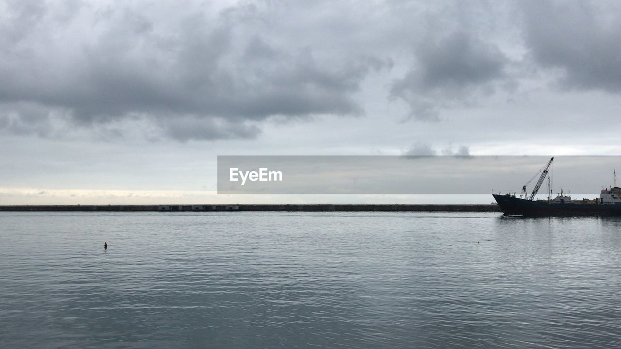water, cloud - sky, sky, nautical vessel, sea, tranquil scene, scenics - nature, transportation, waterfront, tranquility, beauty in nature, mode of transportation, nature, no people, day, overcast, non-urban scene, travel, outdoors, sailboat, anchored