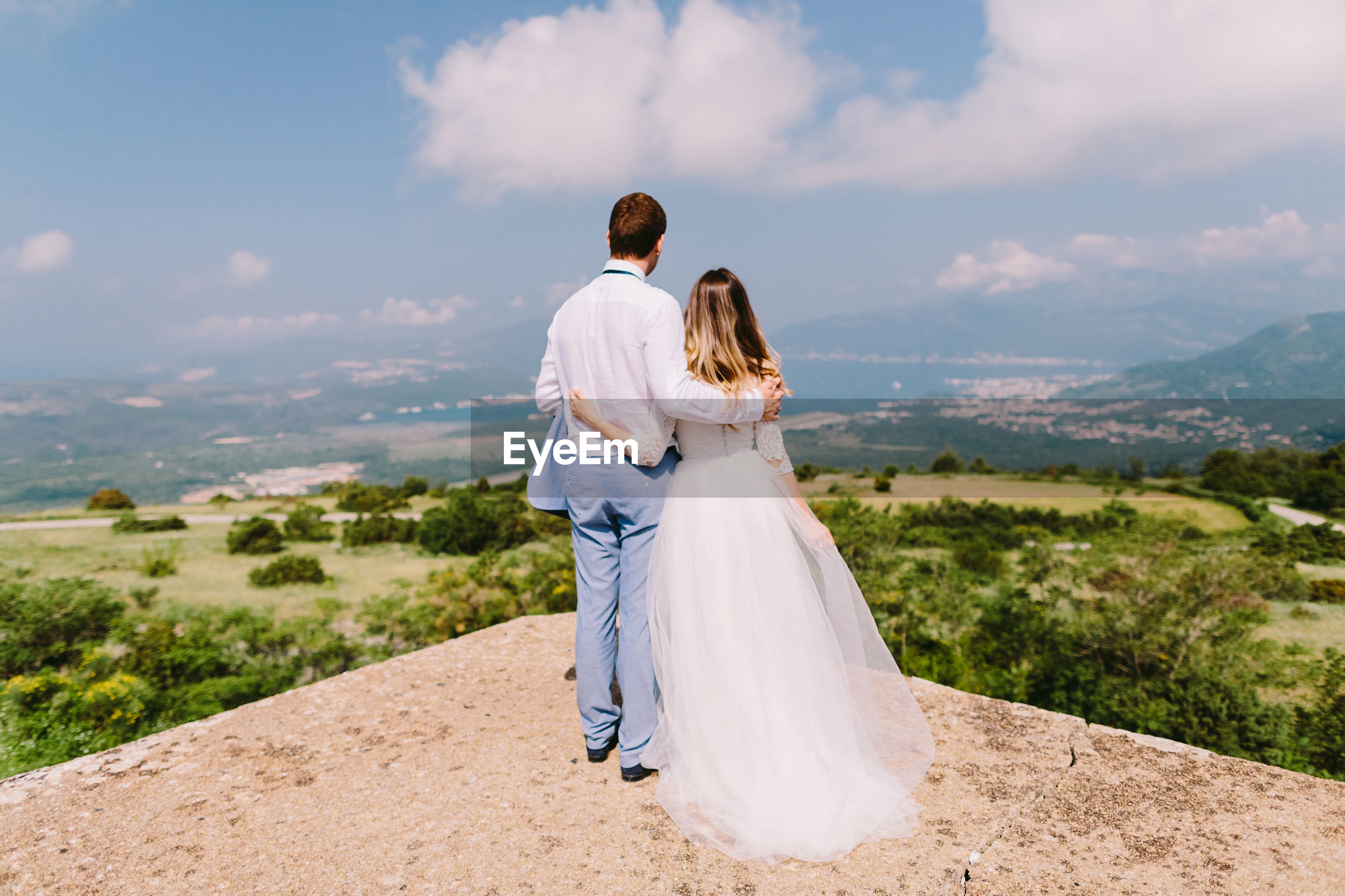 Rear view of married couple standing at observation point against sky