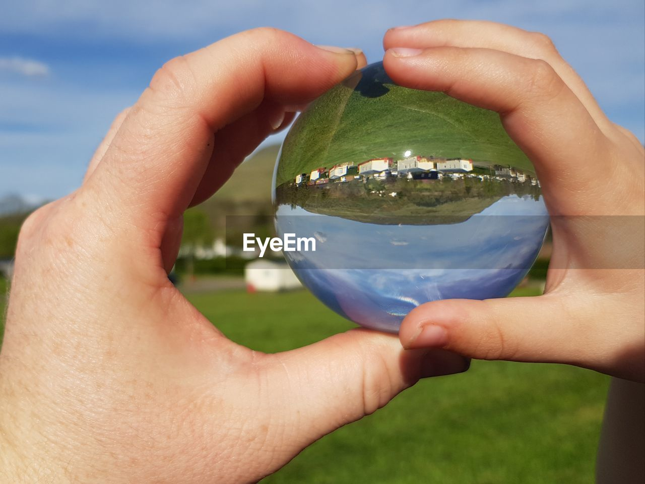 Close-up of person hands holding crystal ball on field