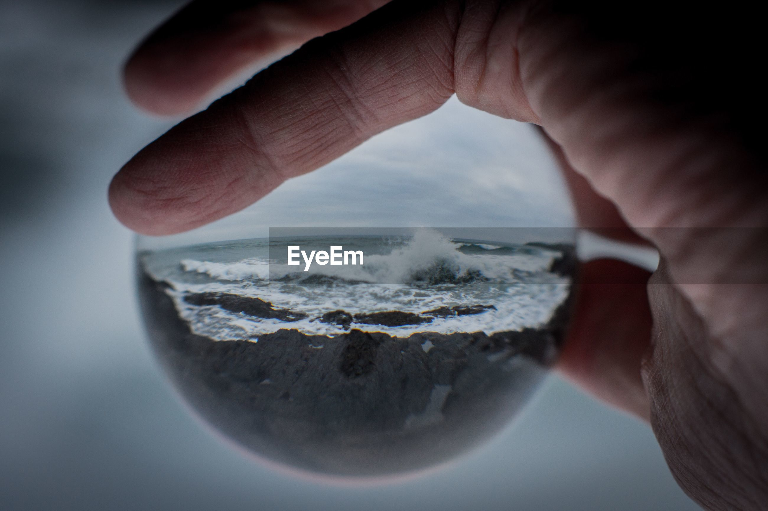 Close-up of human hand holding crystal ball against sea
