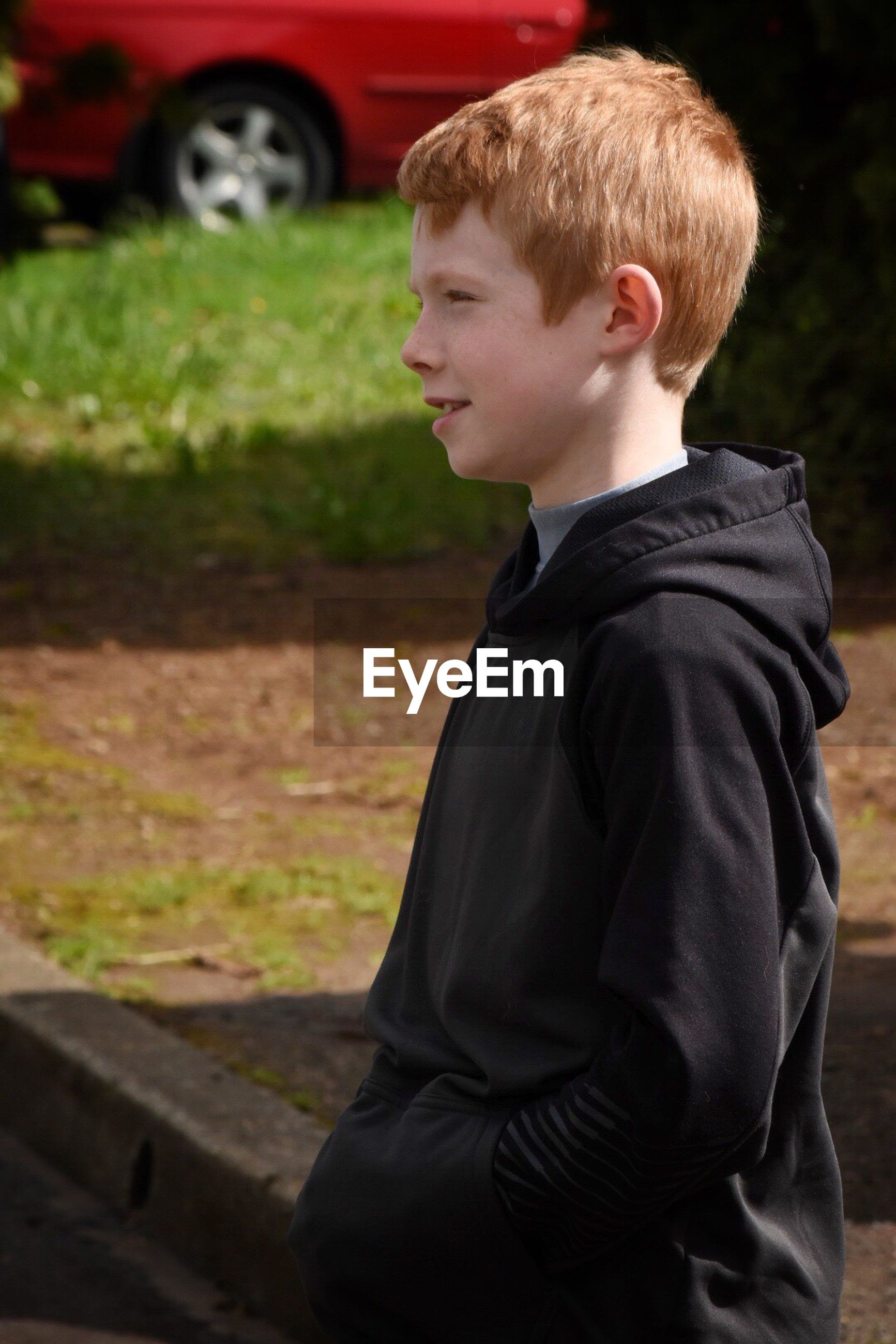 Side view of boy looking away while standing on field