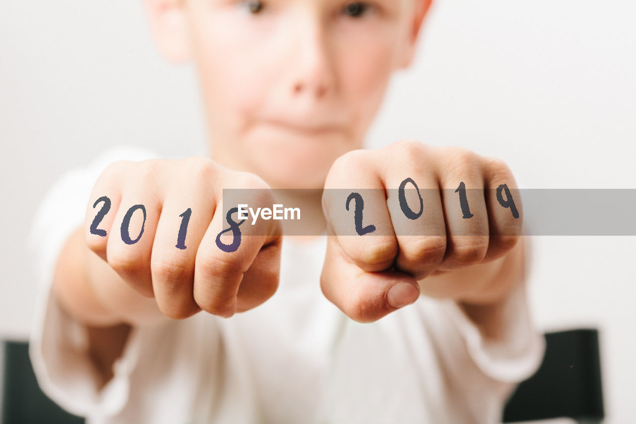 Close-Up Portrait Of Boy Showing Numbers On Fists At Home