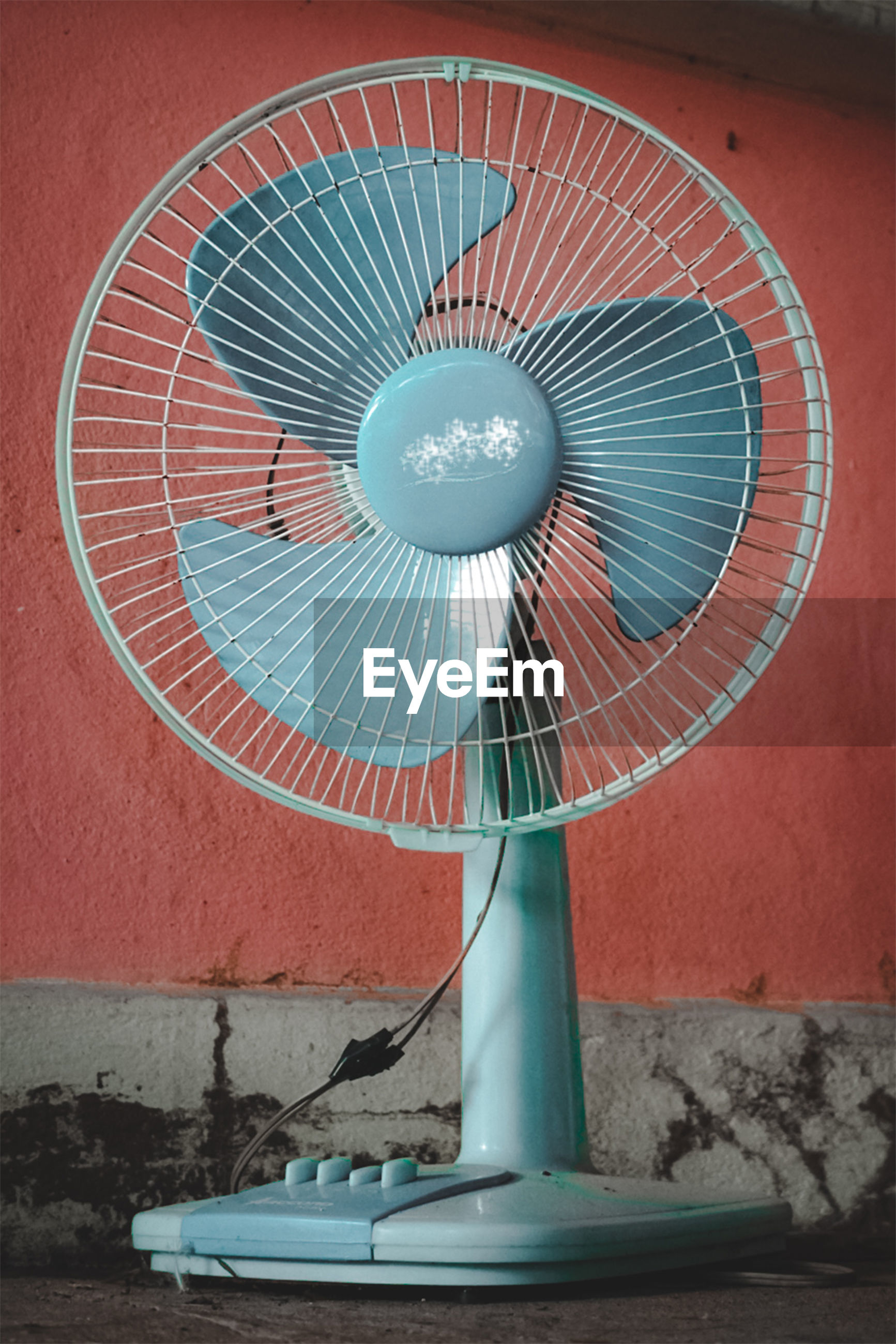 CLOSE-UP OF ELECTRIC FAN ON WALL