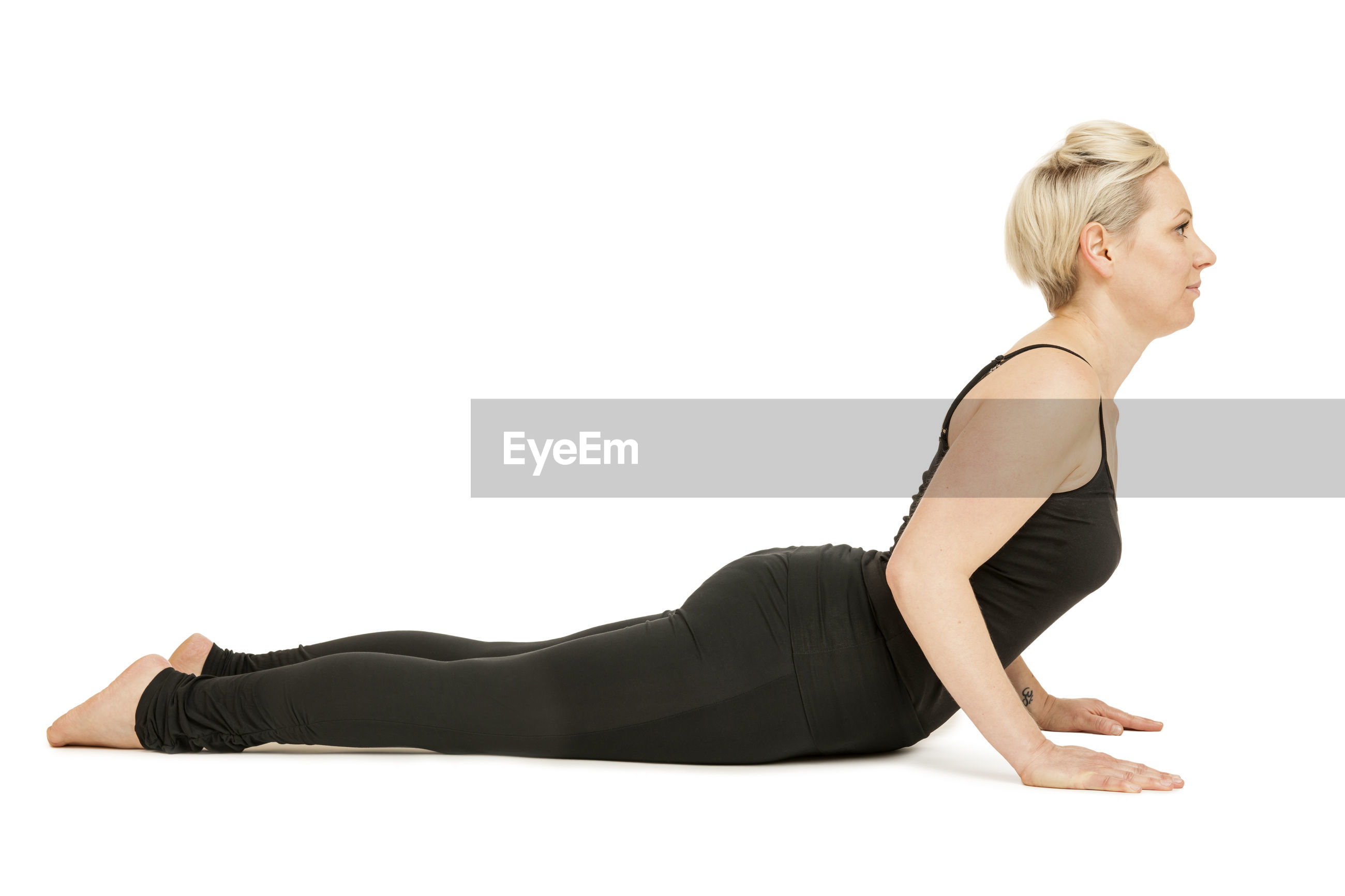 Full length side view of mid adult woman practicing yoga against white background