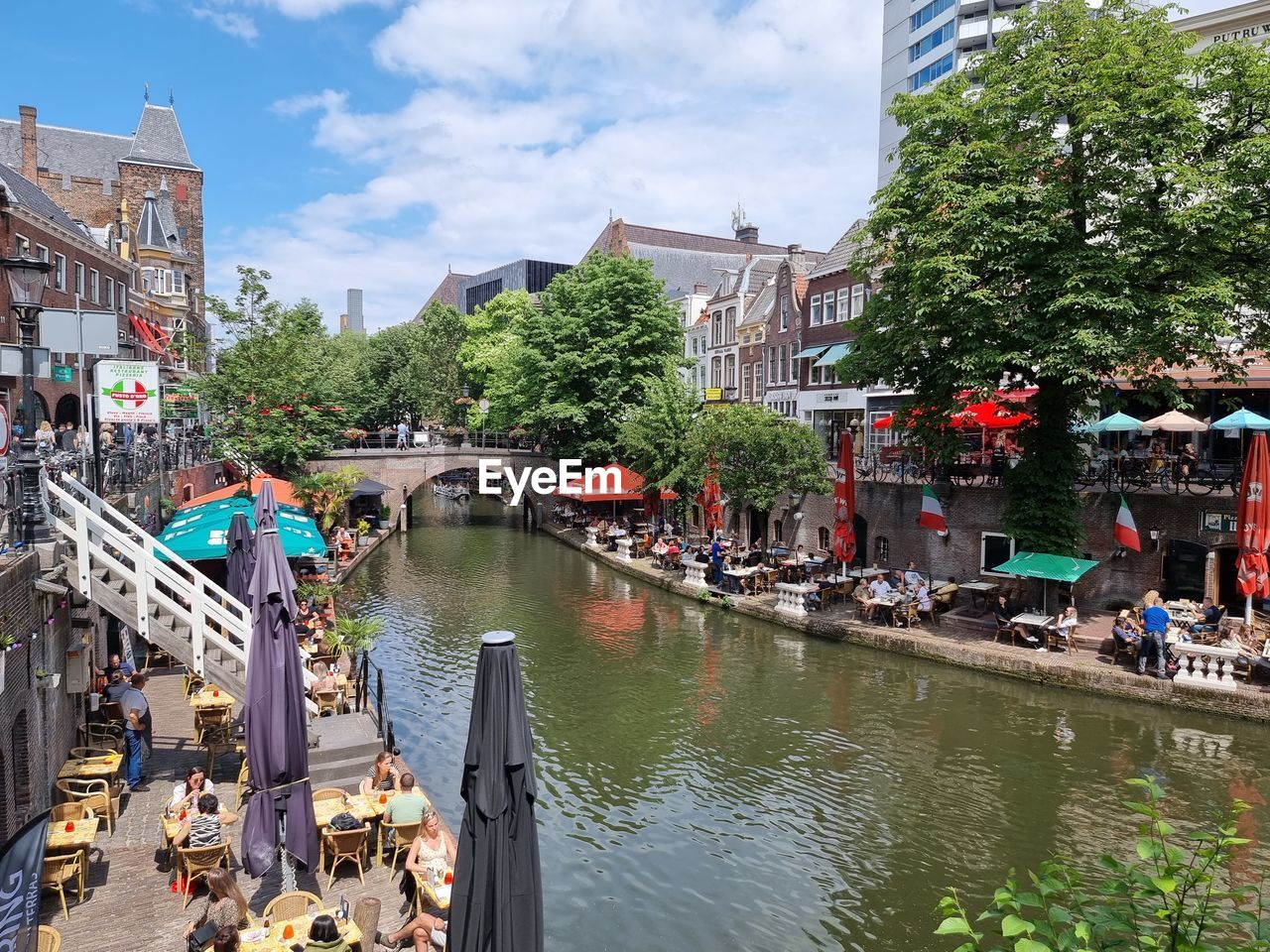 PANORAMIC VIEW OF PEOPLE ON BRIDGE OVER CANAL AMIDST BUILDINGS IN CITY
