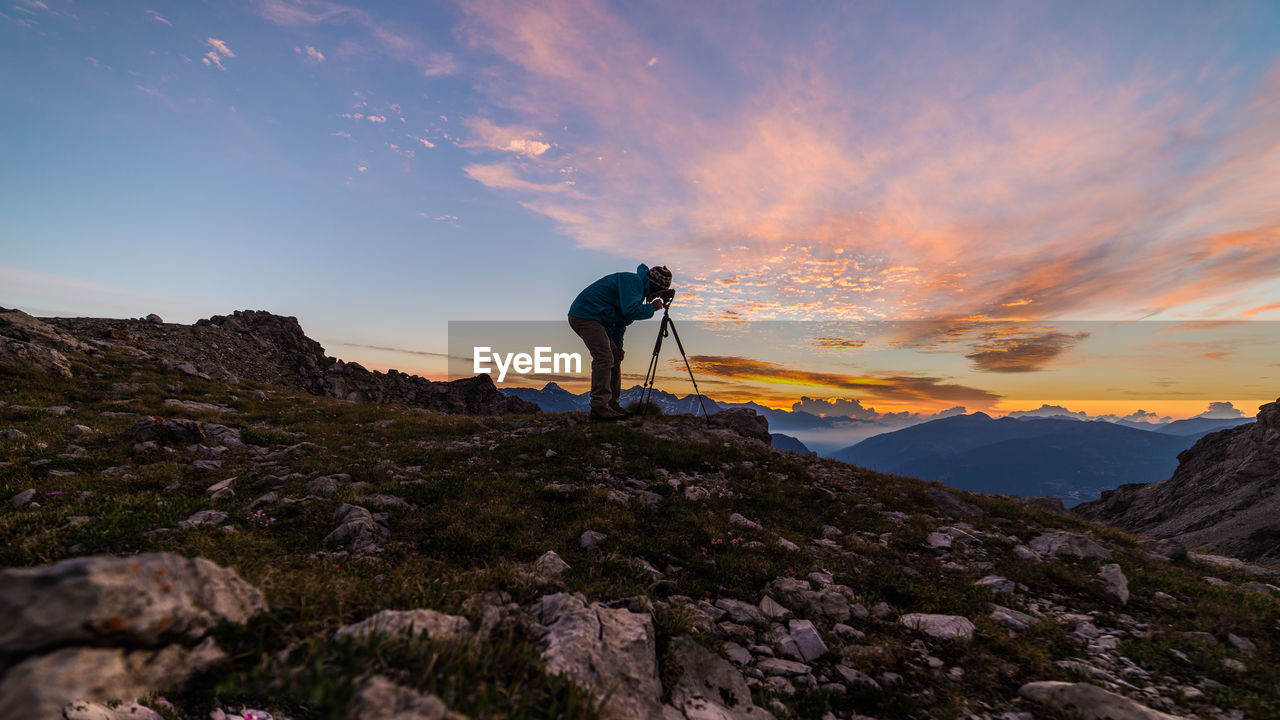 Side View Of Man Photographing On Mountain Against Sky During Sunset