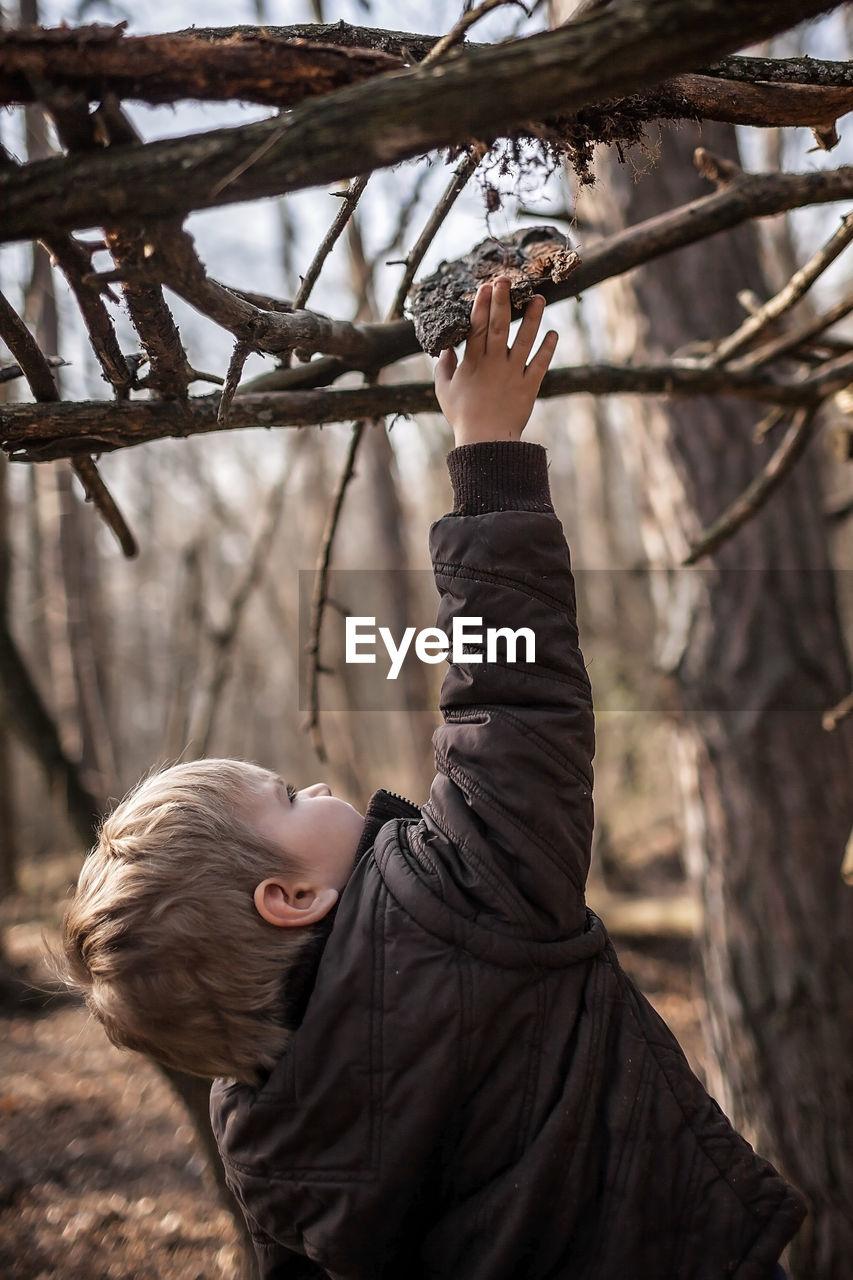 PORTRAIT OF BOY HOLDING PLANT AGAINST TREES