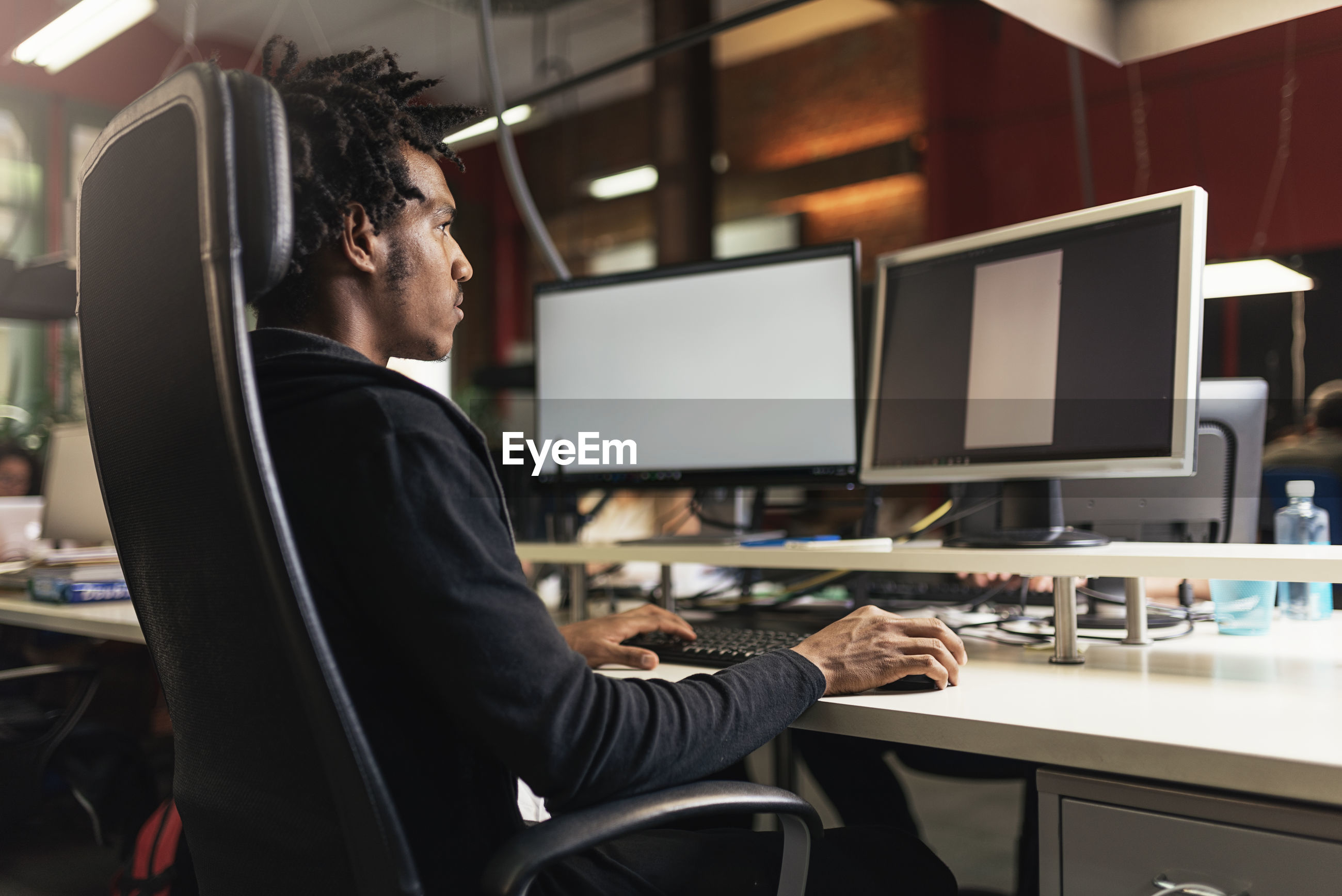 Man using computer at desk in office