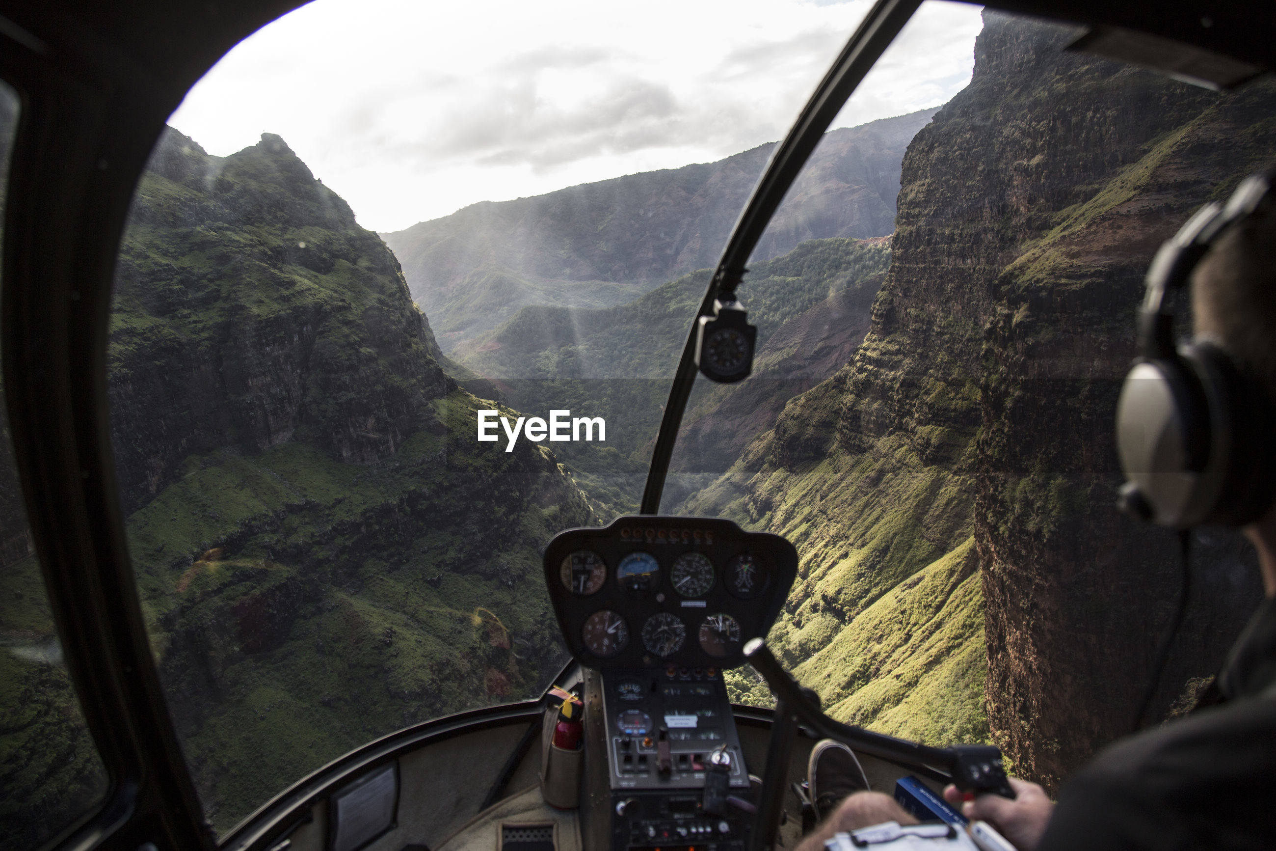 vehicle interior, transportation, mountain, mode of transport, day, windshield, cockpit, landscape, helicopter, one person, real people, window, air vehicle, sky, steering wheel, mountain range, tree, flying, indoors, nature, pilot, close-up, people