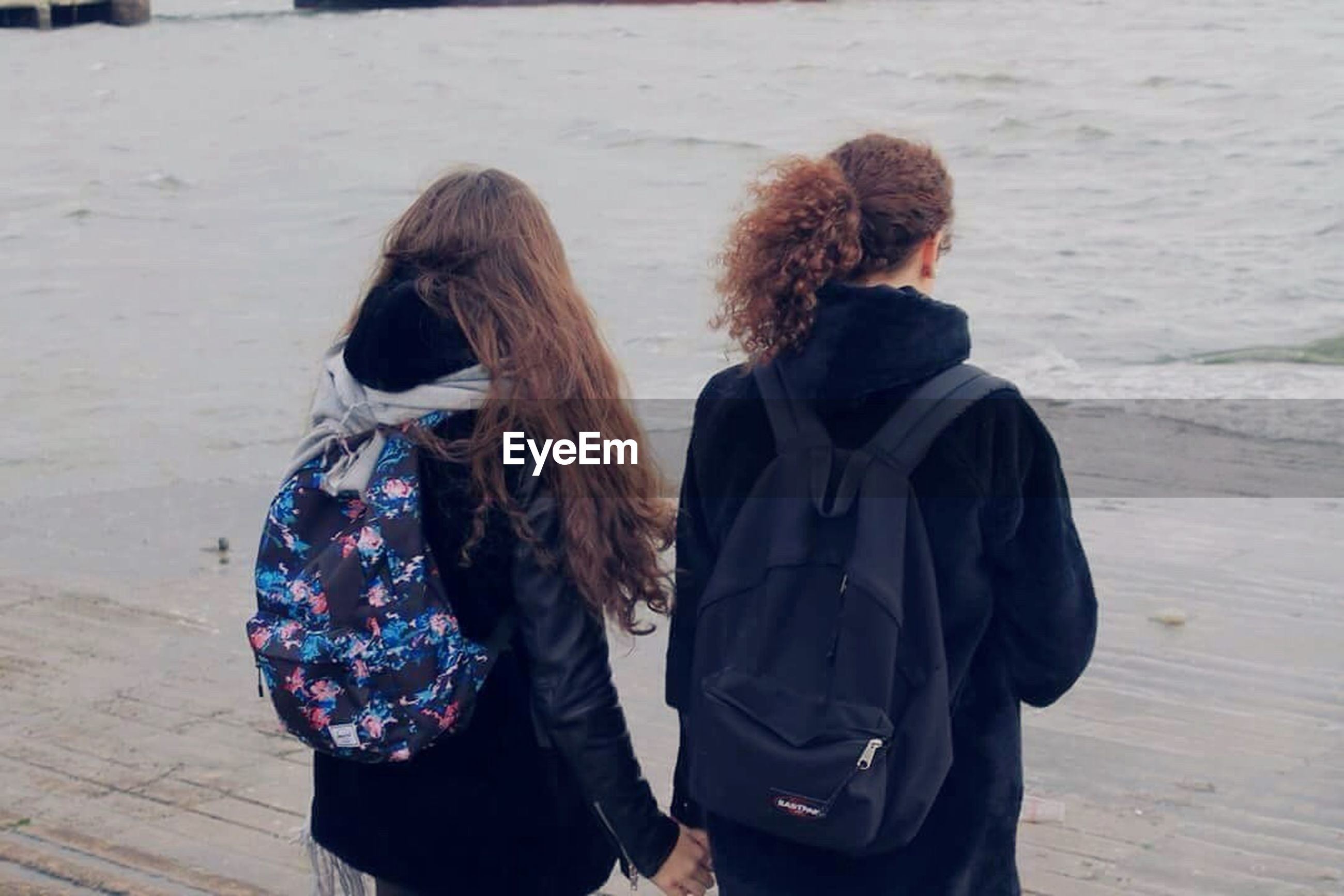 two people, long hair, friendship, leisure activity, togetherness, rear view, standing, young women, only women, beach, curly hair, adults only, outdoors, cold temperature, people, young adult, day, adult