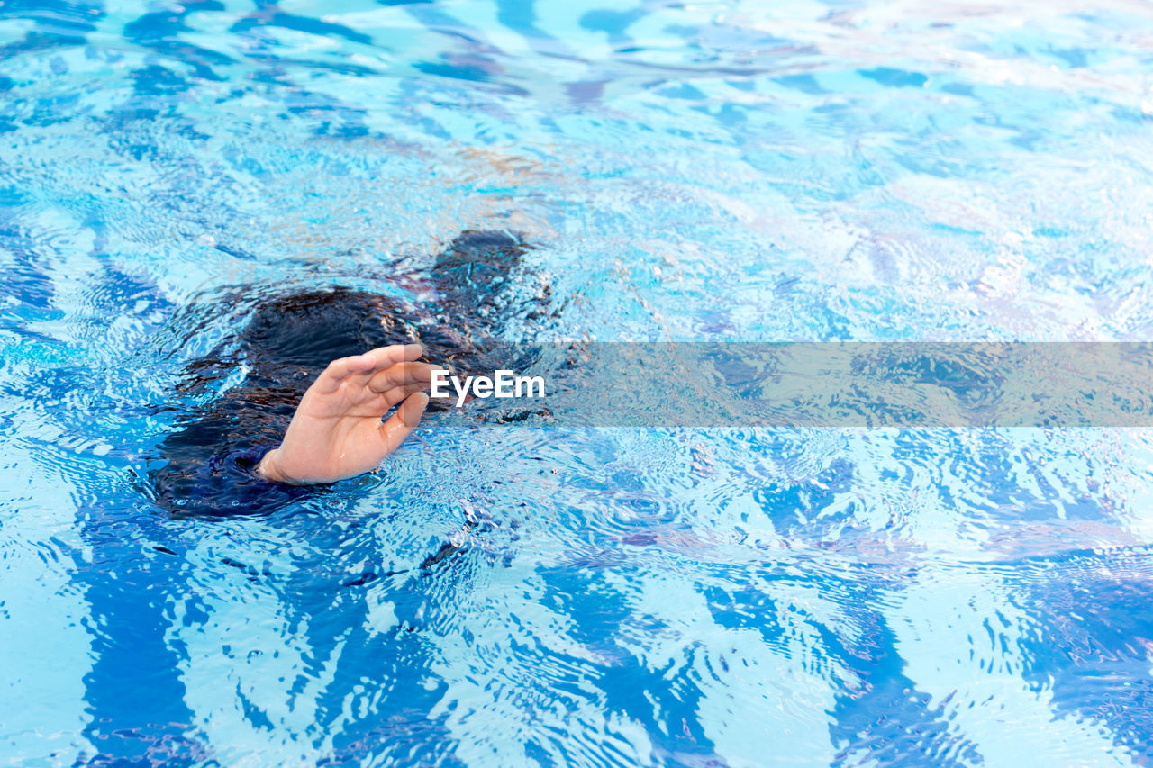 pool, water, swimming pool, one person, blue, high angle view, day, nature, waterfront, leisure activity, real people, rippled, swimming, human body part, outdoors, floating, lifestyles, body part, floating on water, purity, human limb