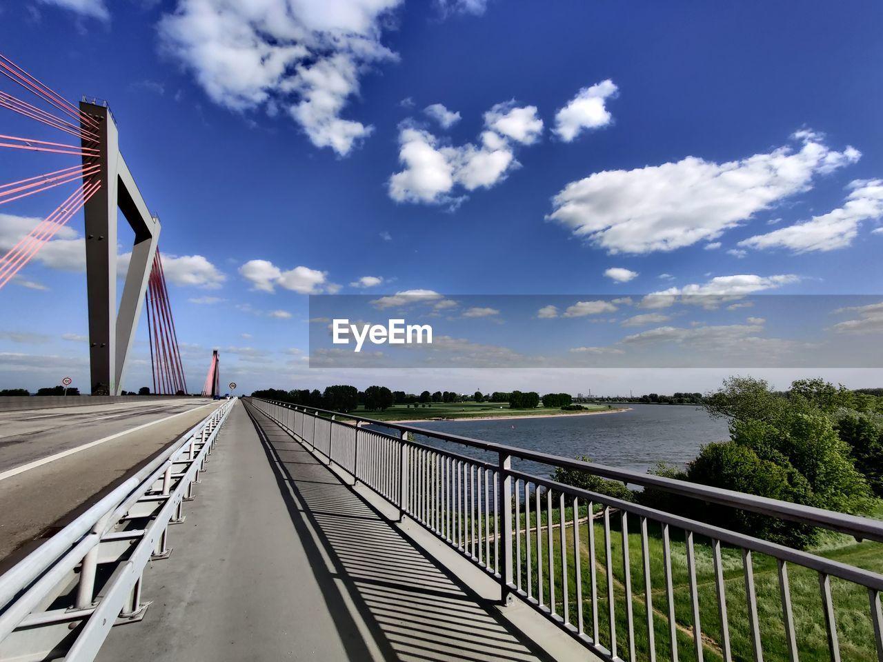 BRIDGE BY RIVER AGAINST SKY