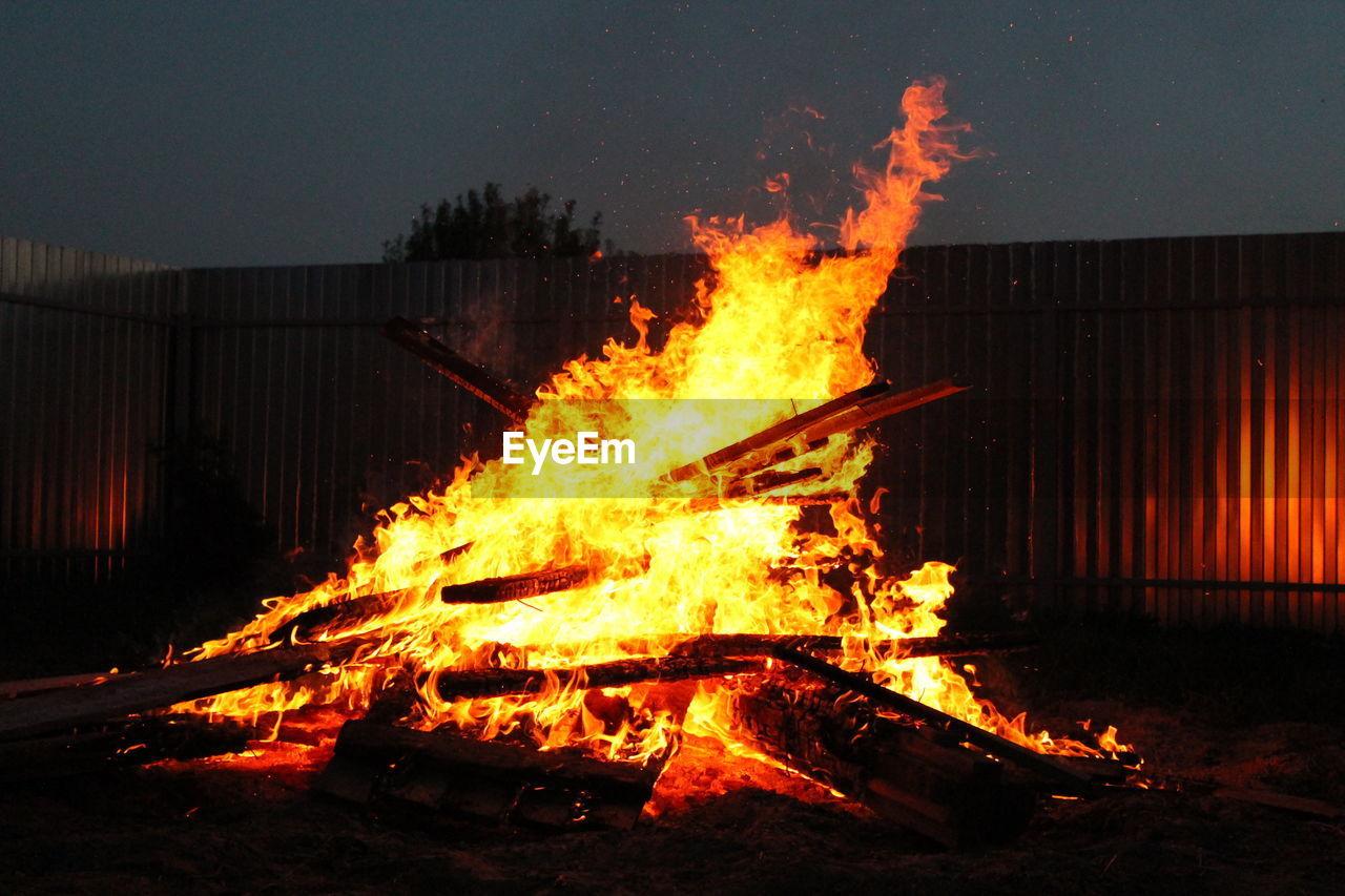 Close-Up Of Bonfire Against Wall At Night