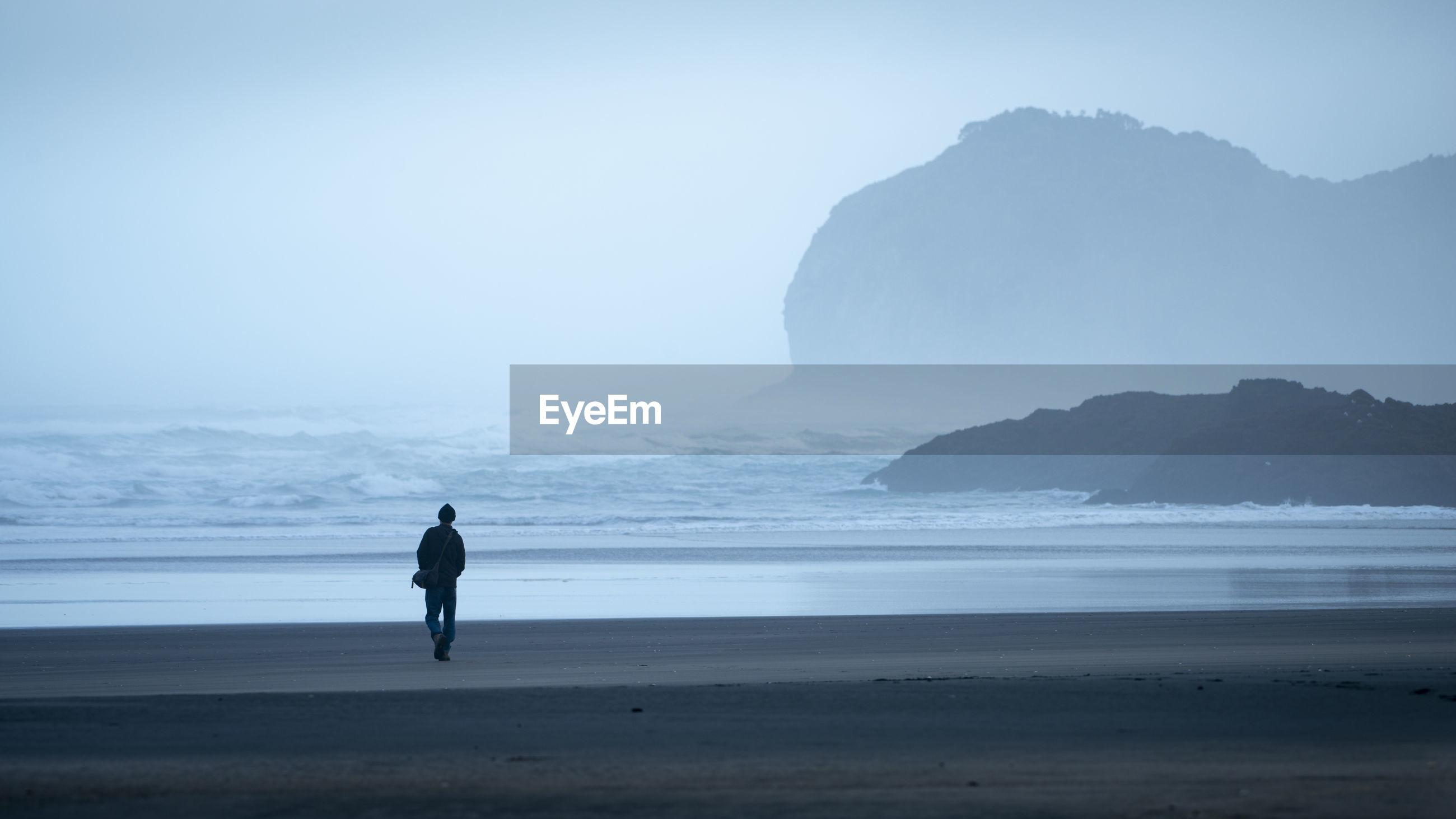Rear view of silhouette man walking at beach