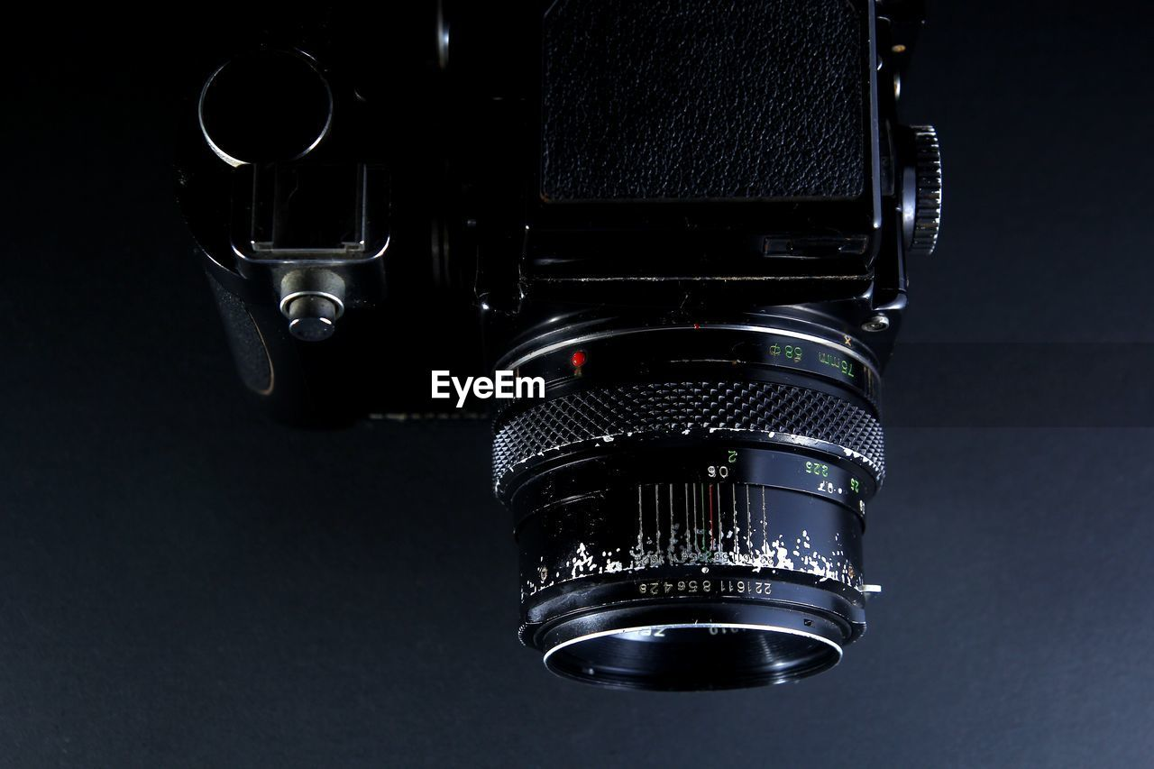 technology, close-up, indoors, photography themes, camera - photographic equipment, no people, photographic equipment, studio shot, black color, digital camera, lens - optical instrument, camera, single object, still life, arts culture and entertainment, black background, lens - eye, equipment, metal, communication