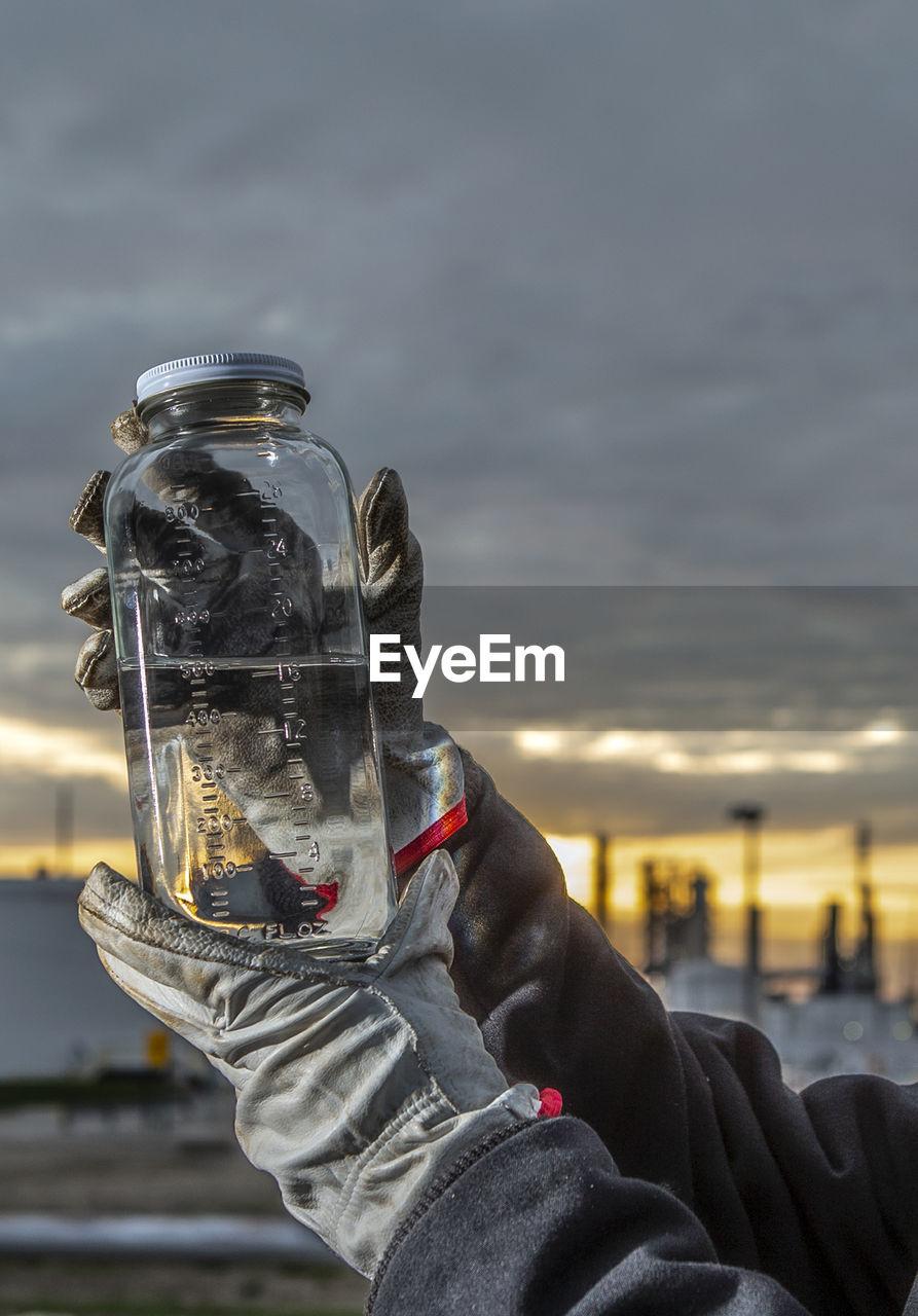 MAN HOLDING GLASS AGAINST SKY