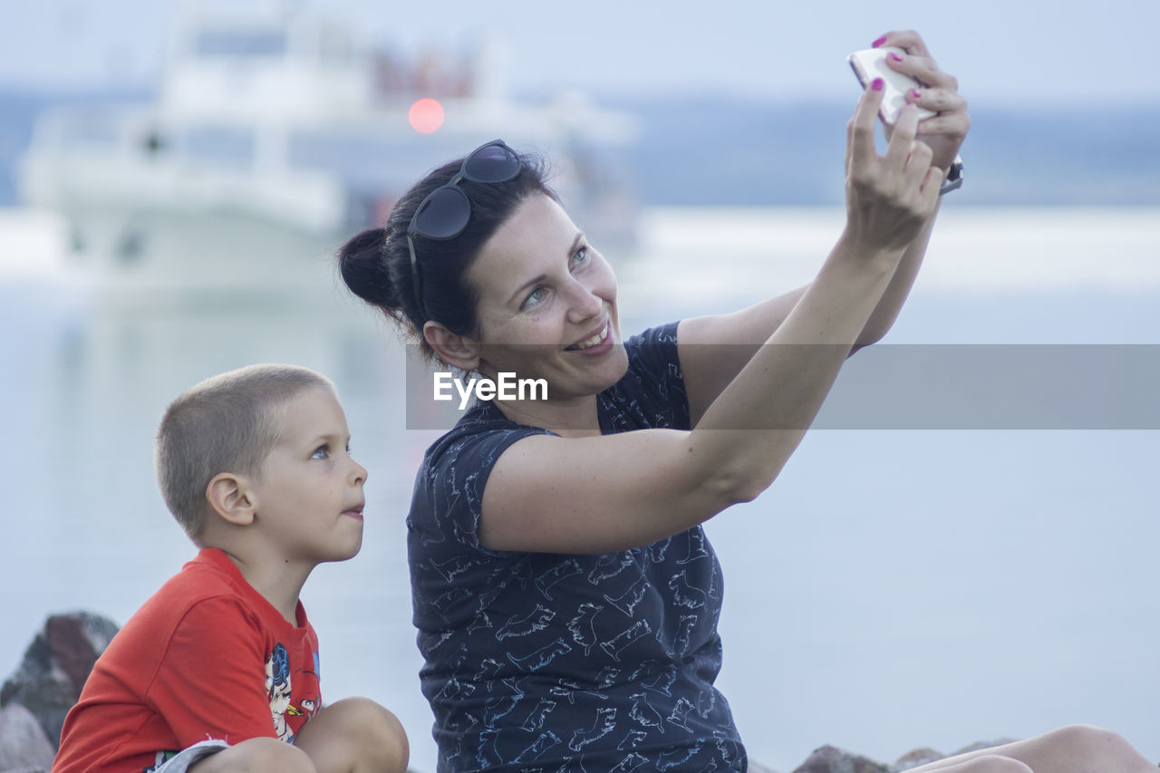 Smiling Woman Taking Selfie With Son By Sea