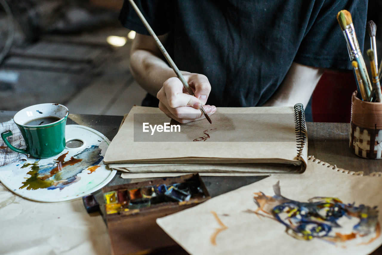 one person, art and craft, craft, real people, occupation, indoors, working, table, creativity, skill, workshop, holding, human hand, hand, craftsperson, making, work tool, selective focus, midsection, workbench, preparation, design professional, tailor