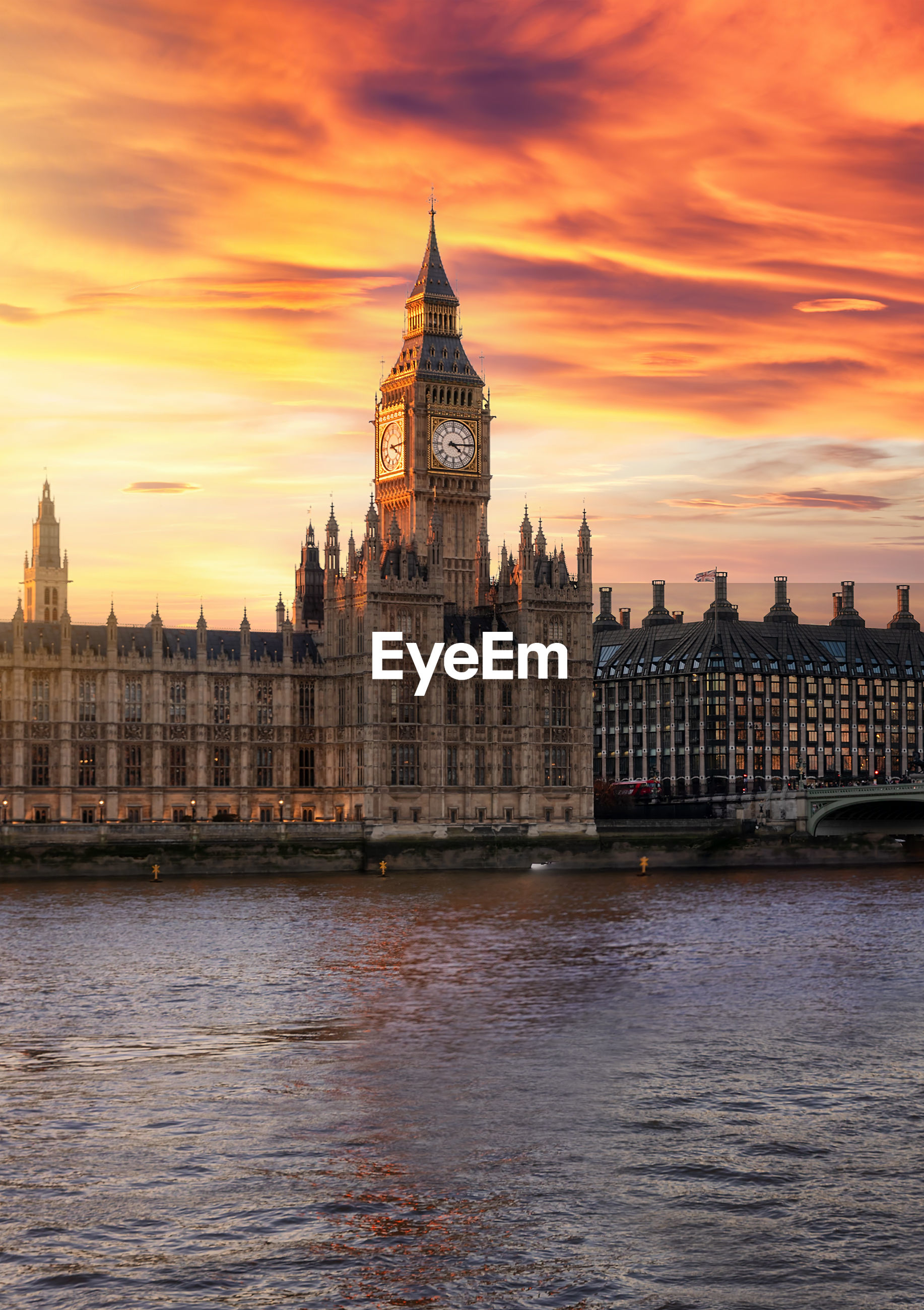 Big ben by thames river against cloudy sky during sunset