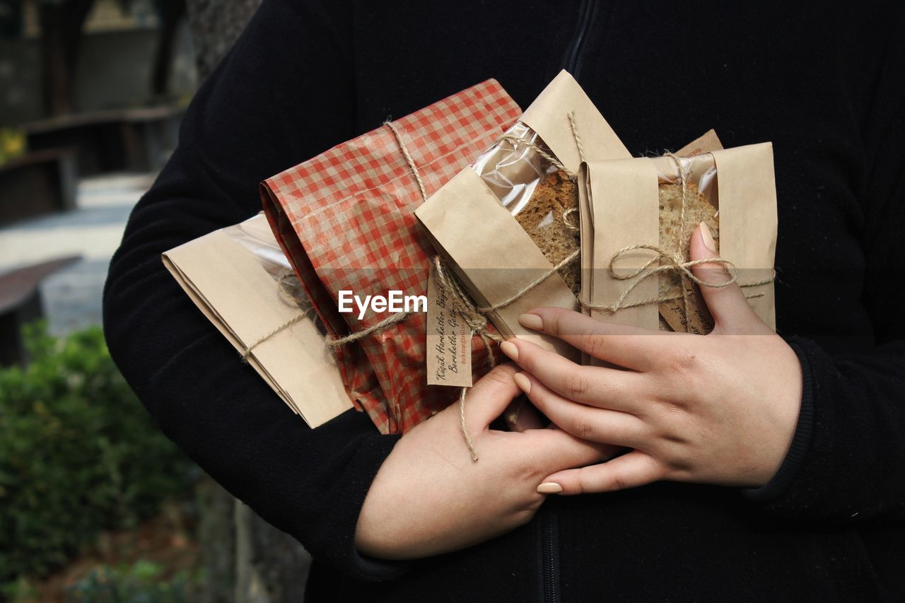 Midsection of woman holding envelope outdoors