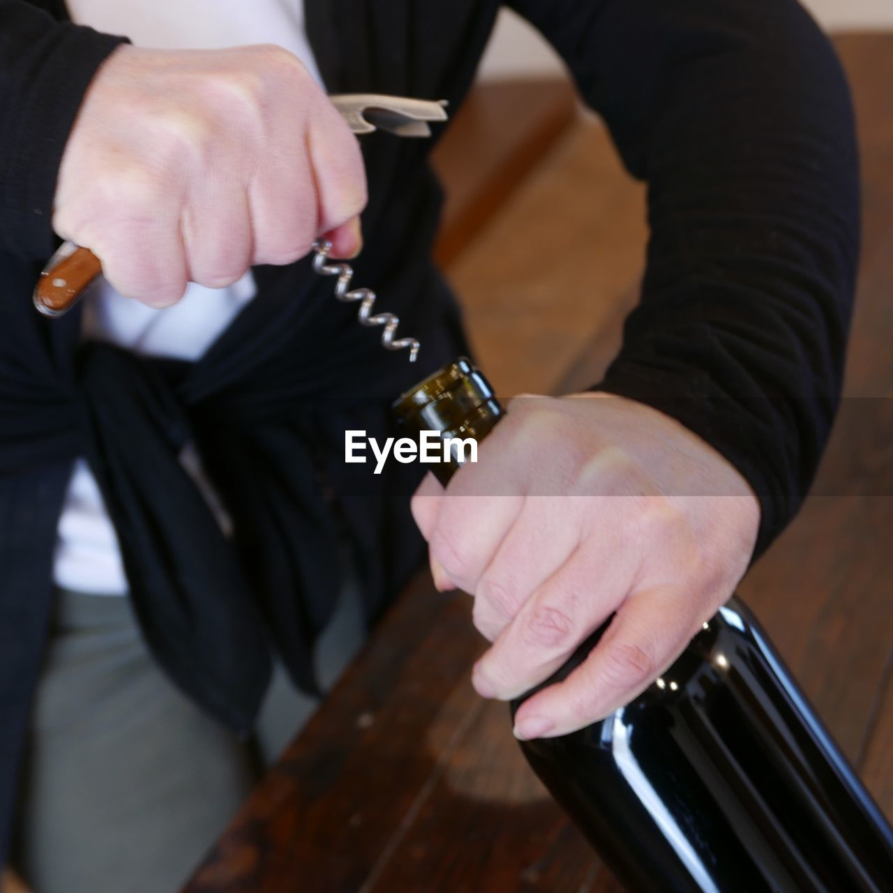 Midsection Of Man Pulling Cork From Wine Bottle