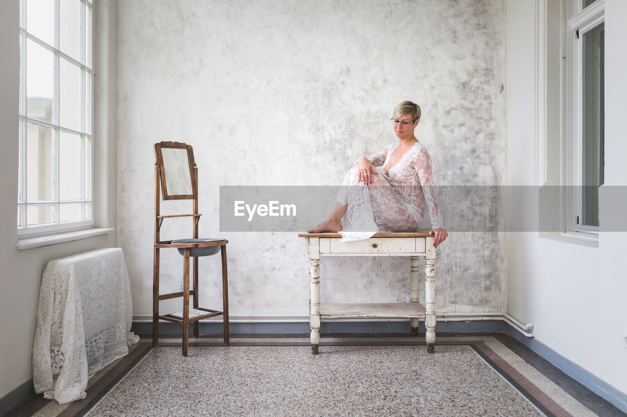 FULL LENGTH OF WOMAN SITTING ON CHAIR IN HOME