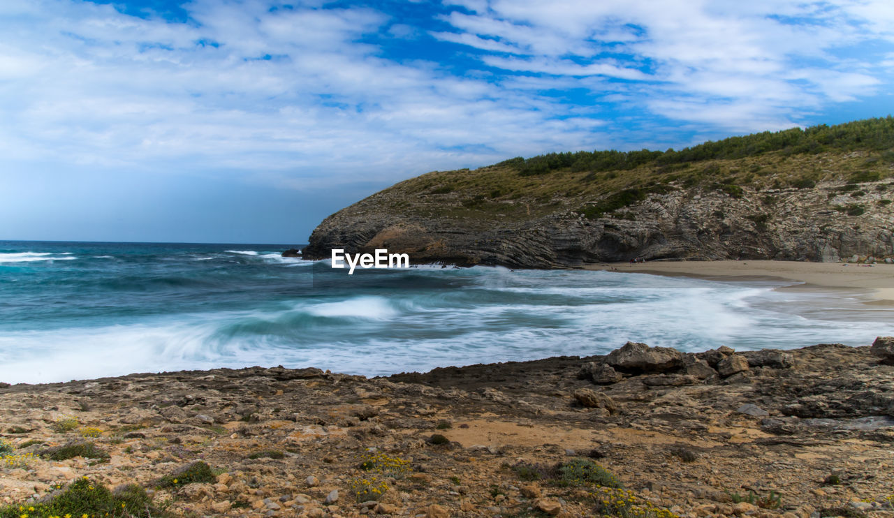 sea, water, sky, cloud - sky, beauty in nature, land, scenics - nature, beach, rock, rock - object, nature, solid, tranquility, motion, day, tranquil scene, horizon, no people, rock formation, horizon over water, outdoors, rocky coastline