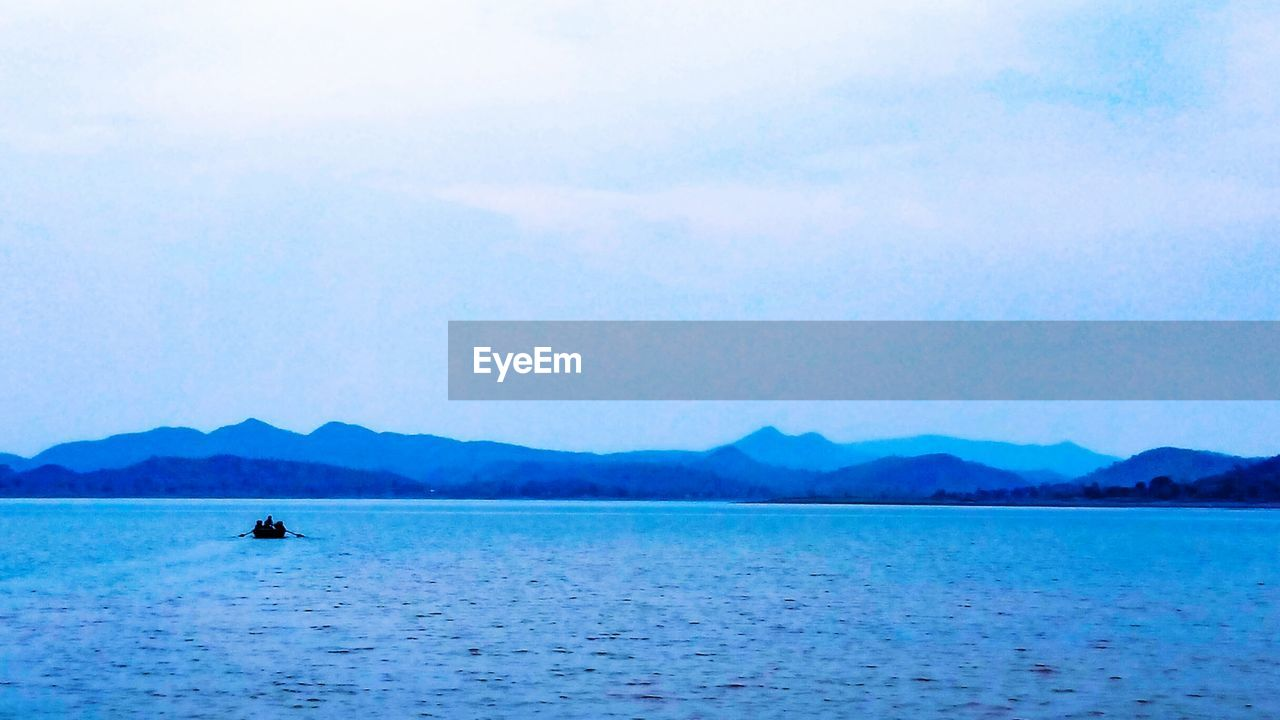 water, scenics, beauty in nature, nature, tranquility, waterfront, mountain, tranquil scene, outdoors, sea, day, sky, nautical vessel, blue, one person, people