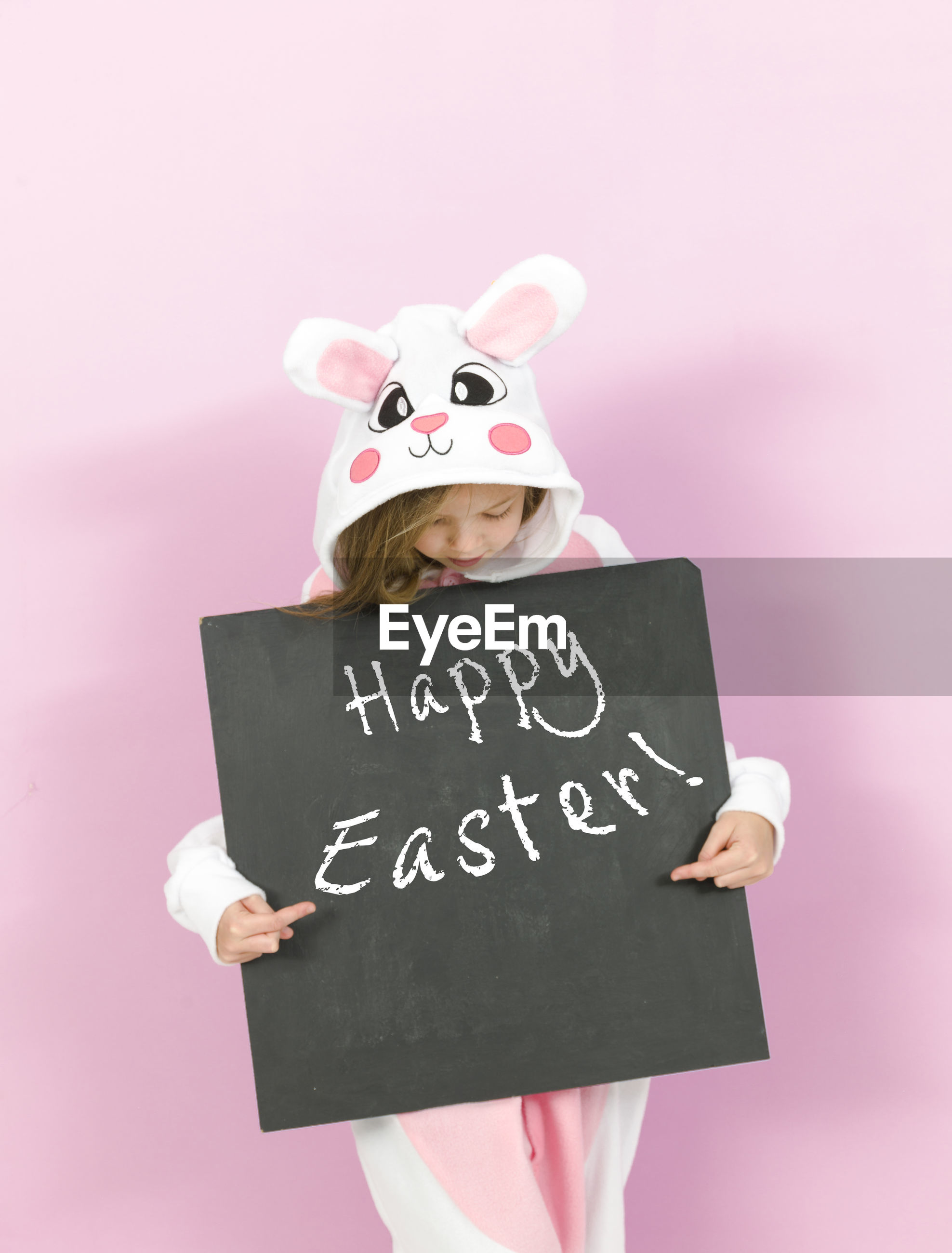 Girl wearing rabbit costume holding writing slate with text against pink background