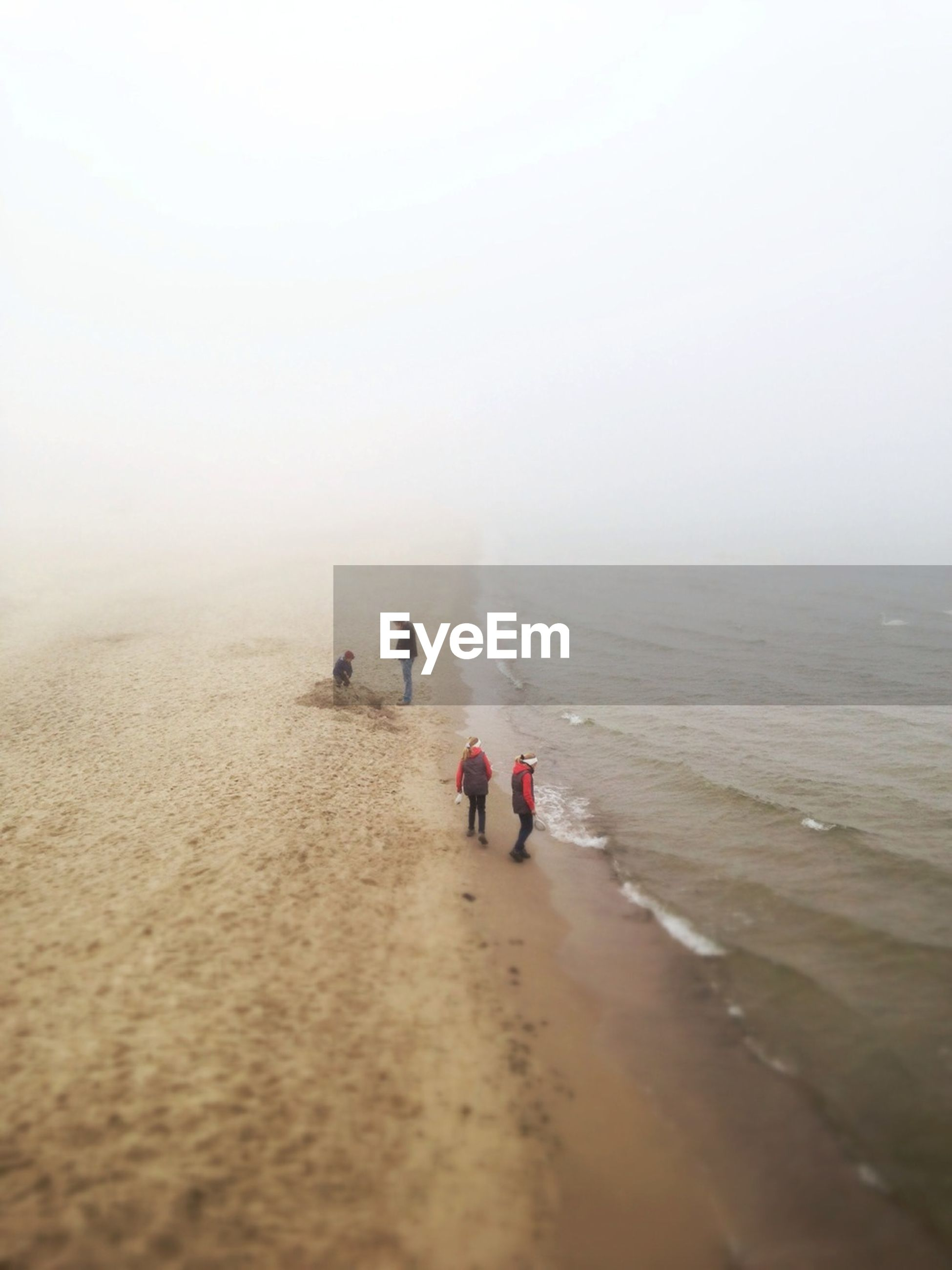 High angle view of people on beach during foggy weather
