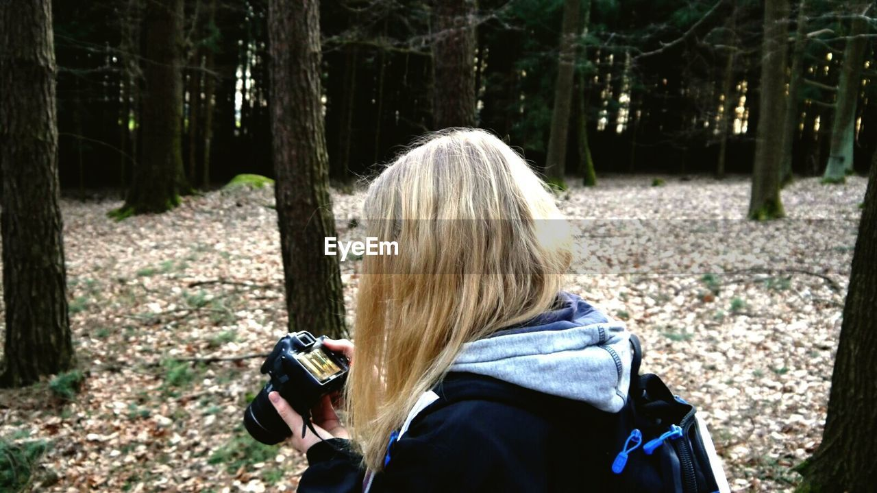 forest, tree, real people, camera - photographic equipment, land, plant, one person, leisure activity, photography themes, activity, nature, lifestyles, photographing, women, tree trunk, photographic equipment, day, hair, technology, woodland, outdoors, photographer, hairstyle, digital camera