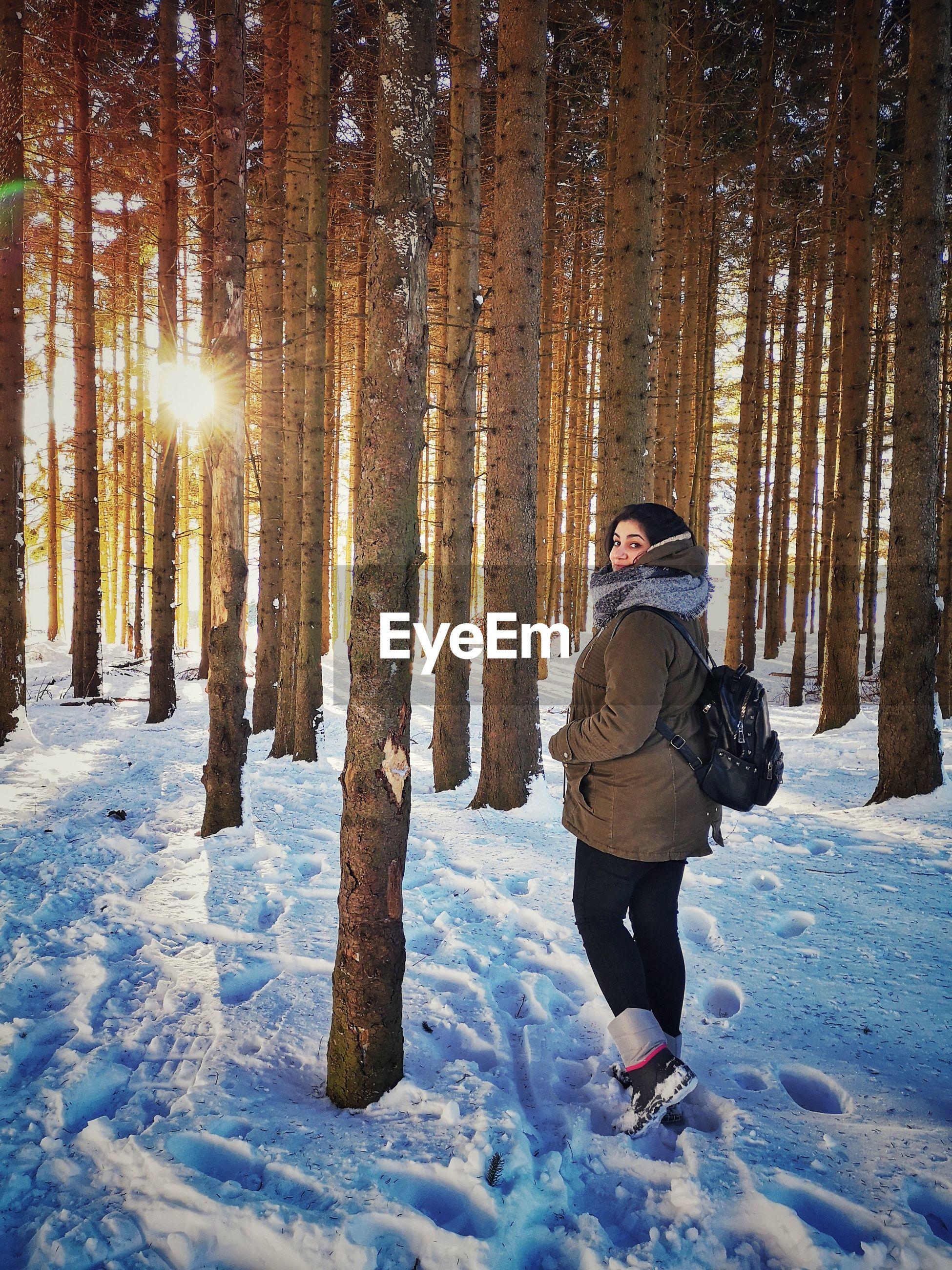 Portrait of woman walking in snowy forest