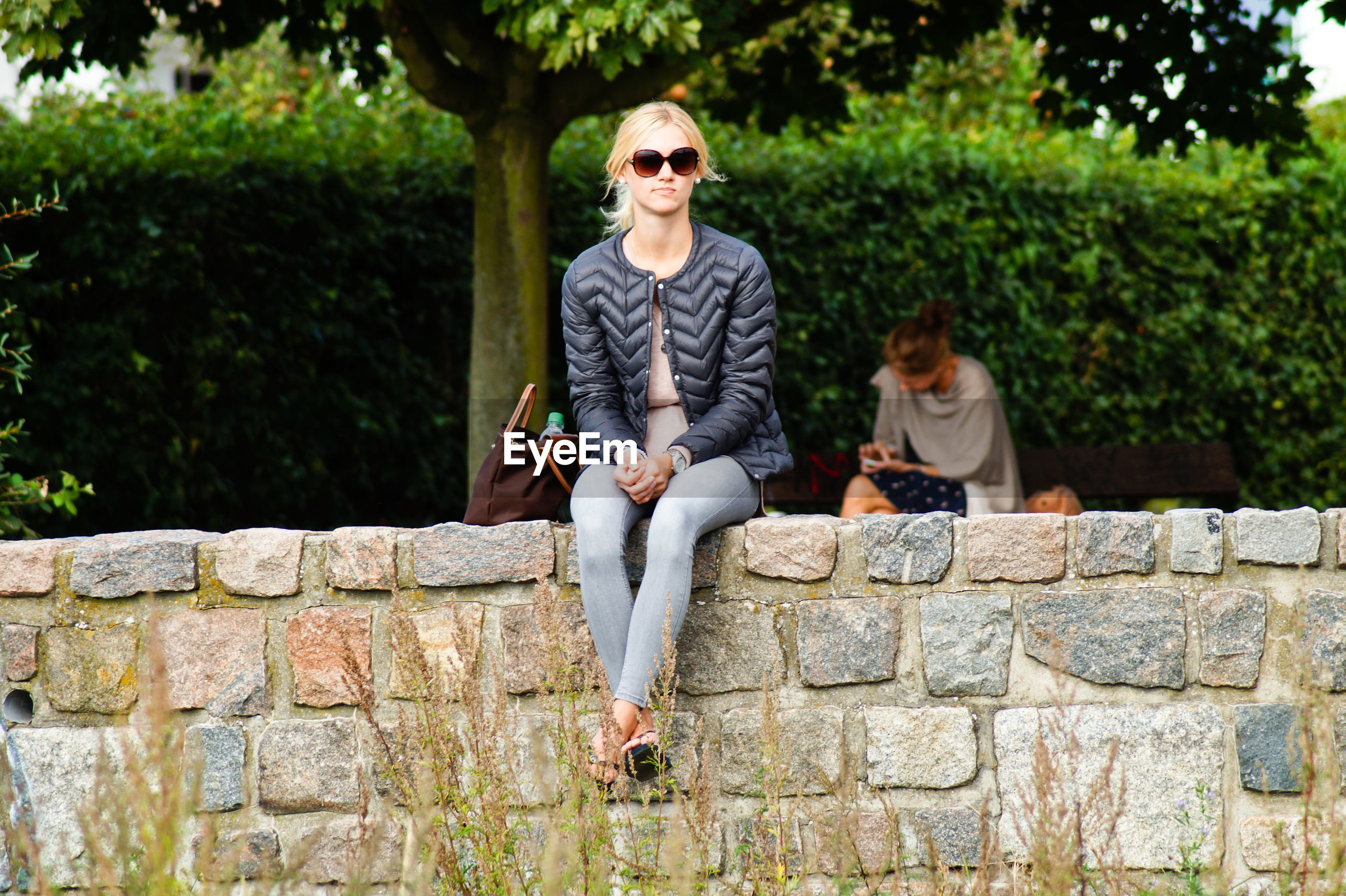Full length of young woman sitting on retaining wall in park