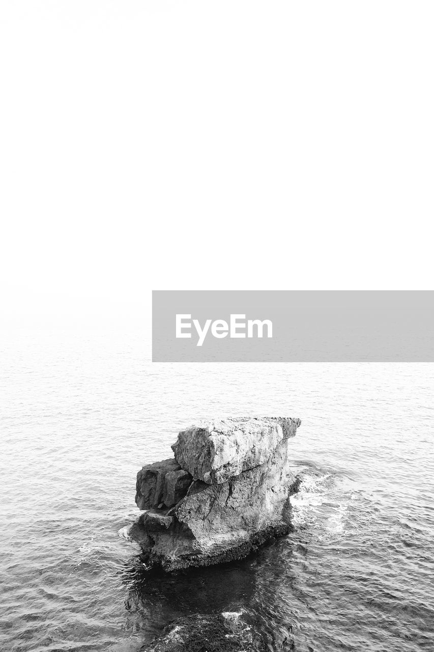 High Angle View Of Rock Structure In Sea Against Clear Sky