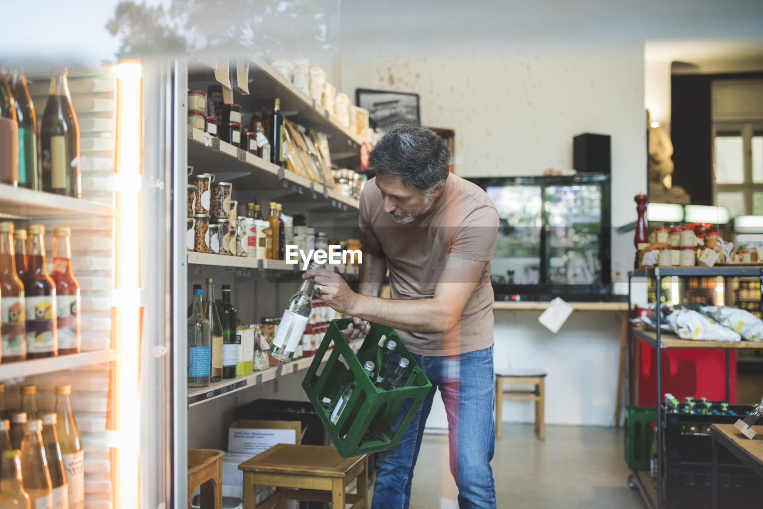 Male employee arranging bottle on shelf in deli