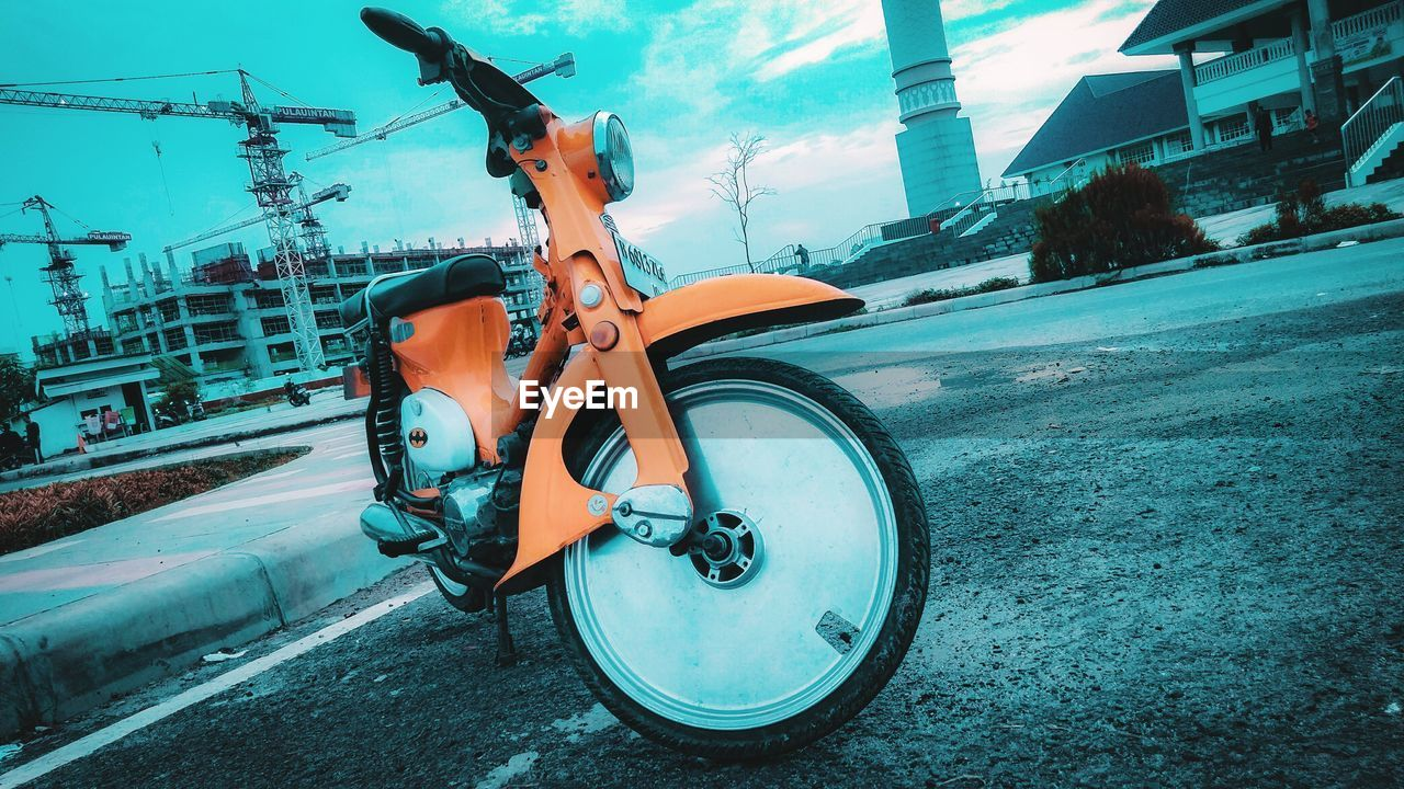 transportation, mode of transportation, land vehicle, street, city, road, day, bicycle, architecture, stationary, building exterior, built structure, scooter, nature, outdoors, sky, travel, no people, motor scooter, machinery, wheel