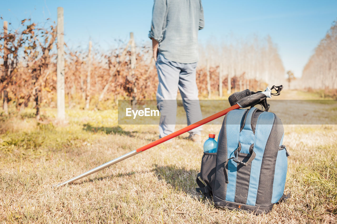 Rear View Of Man With Bag And Hiking Pole On Field