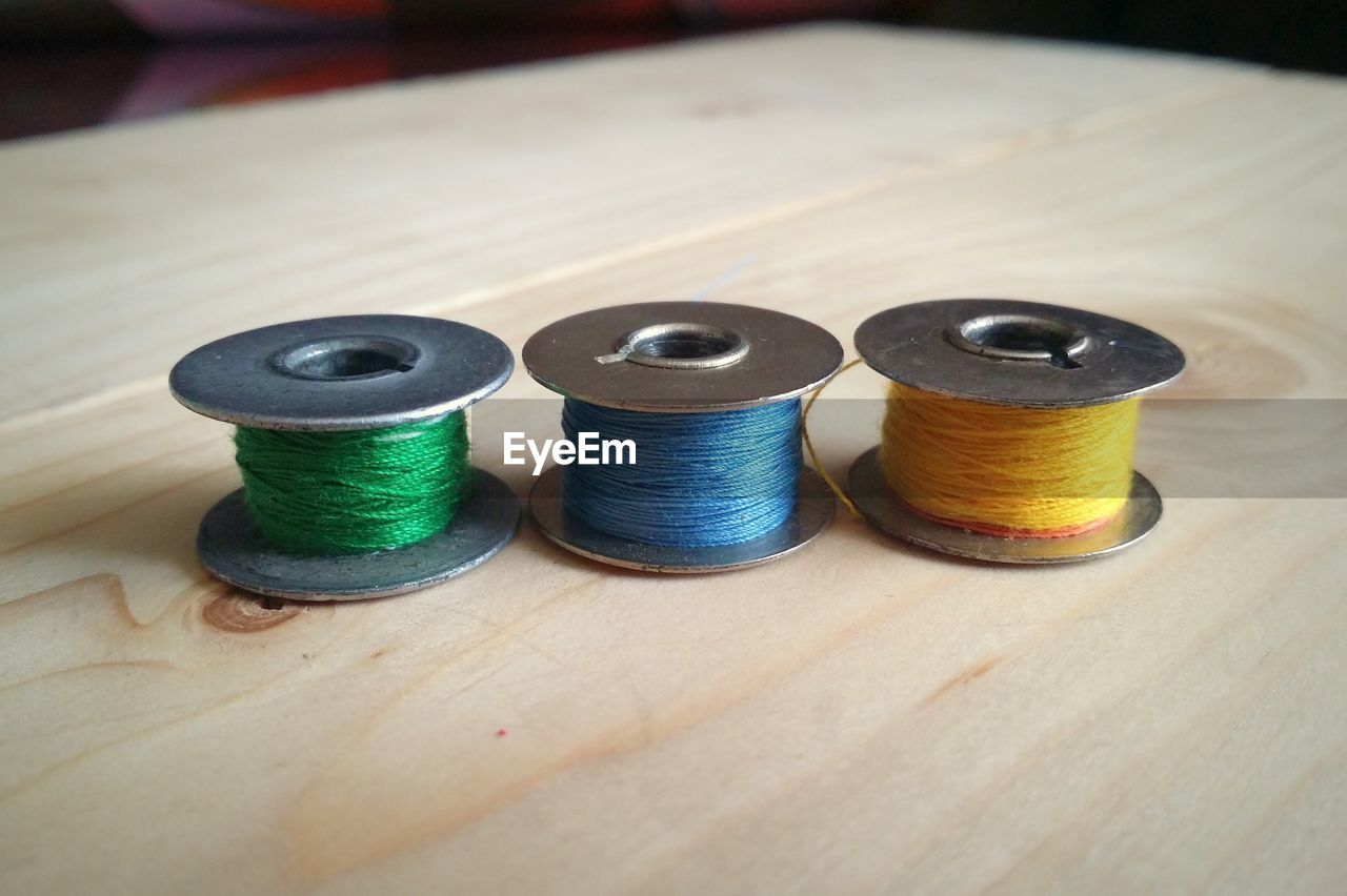 spool, thread, still life, indoors, textile, table, art and craft, sewing item, focus on foreground, multi colored, wood - material, variation, choice, sewing, industry, textile industry, close-up, high angle view, selective focus, needlecraft product, embroidery