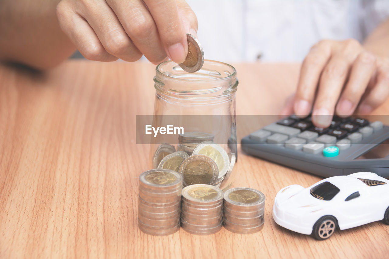 Midsection of person putting coins in glass jar by toy car and calculator on table