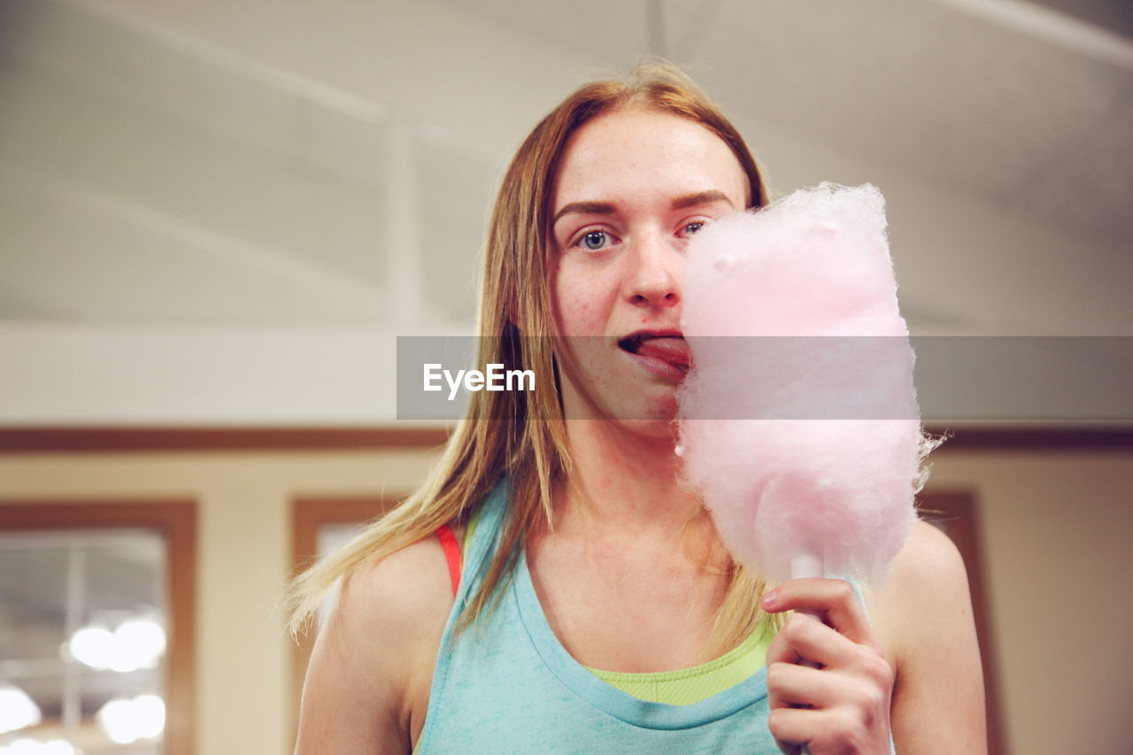 Portrait Of Young Woman Licking Cotton Candy At Restaurant